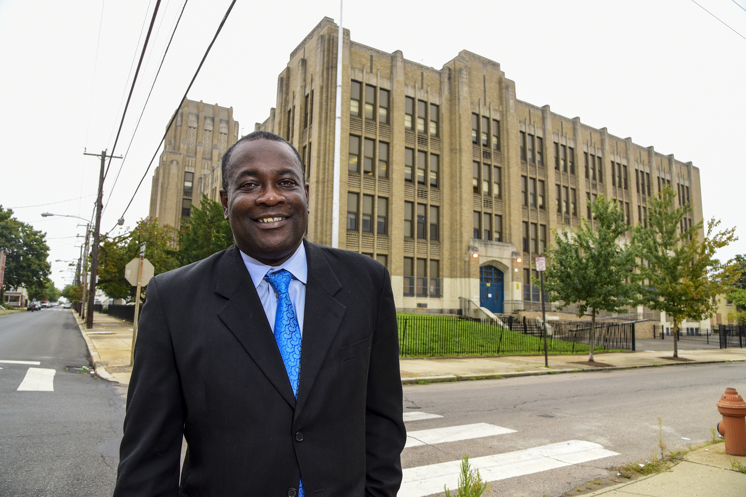 Philadelphia Housing Authority President Kelvin Jeremiah stands outside Vaux Big Picture High School, which PHA bought and is investing millions in as part of a plan to transform Sharswood.