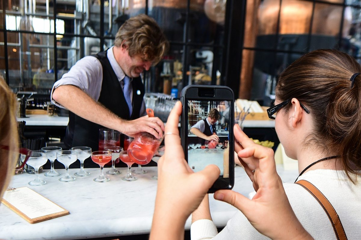 Jack Falkenback, a bartender at Philadelphia Distilling, is photographed by a member of the Association of Food Journalists as he makes drinks.