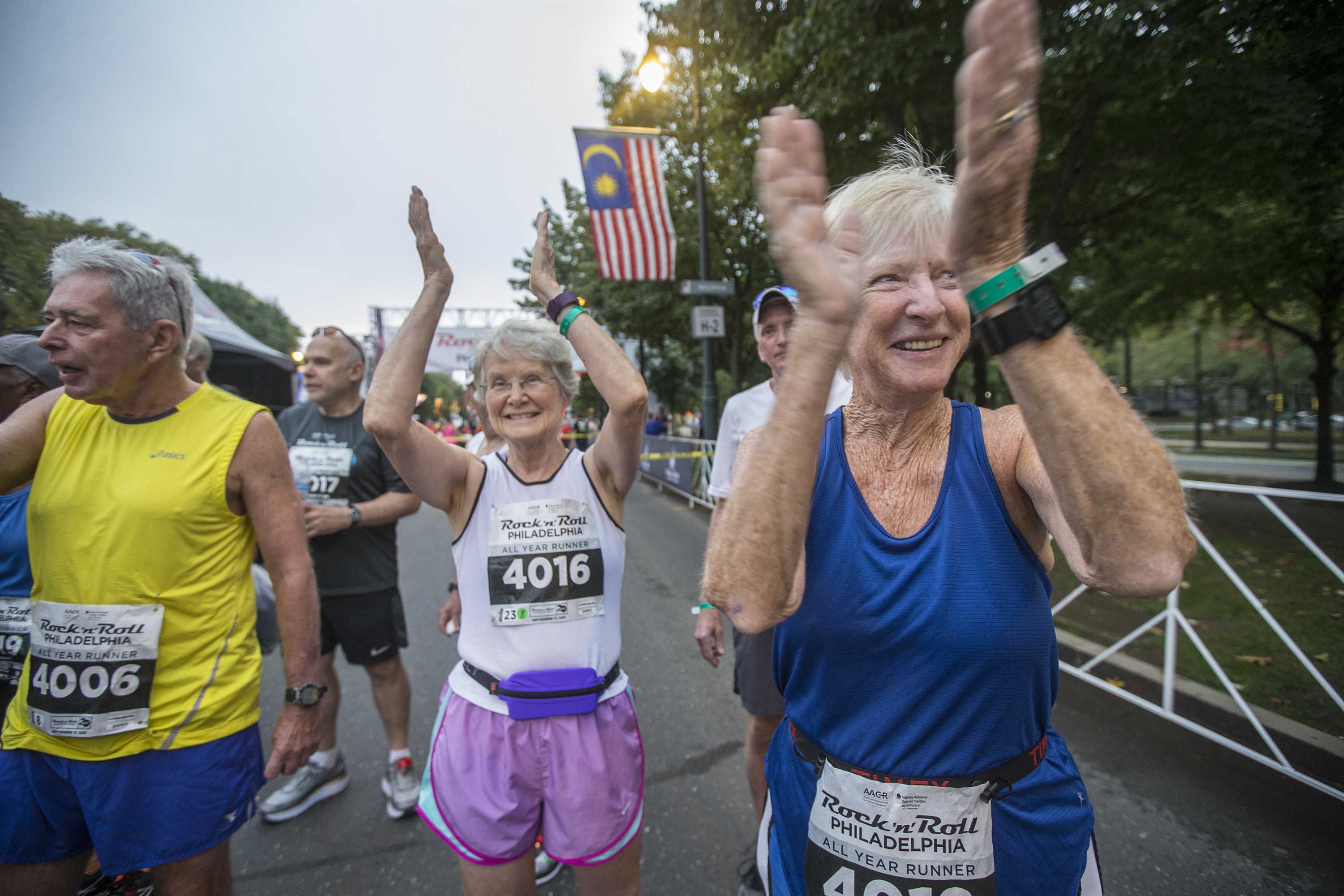 Tina Johnson, right, who now lives in Winter Garden FL, and Nancy English, of Swarthmore, PA, center, clap for their fellow runners that have competed in every Rock and Roll Half Marathon for the past 40 years. For 23 runners -- AGES 58 to 87 -- this Sunday´s Rock n Roll half marathon is way more special than just 13.1 milesit will be each person´s 40th half marathon in Philly!!!!!!! MICHAEL BRYANT / Staff Photographer
