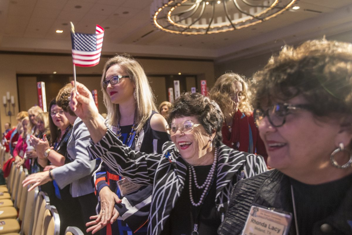Juandelle Roberts, center, from Midland, Texas, waves her American flag as she, the Texas delegation, and the entire general assembly give Carrie Almond, the president of the National Federation of Republican Women, a standing ovation at the beginning of the general session on Sunday in Philadelphia.