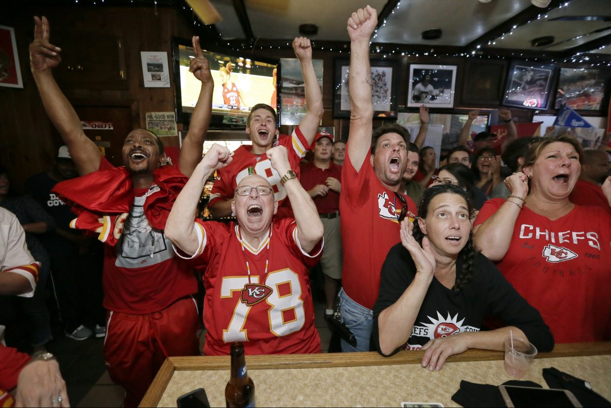 From left: Moe Warwick of West Philadelphia, Steve Barker of Sacremento, Calif., Chris Stanton of Jenkintown, Michele Chermela — an Eagles fan — of Willow Grove, and Lindsi Dull of Akron, Pa. cheer for their teams in the closing moments of the Eagles-Chiefs  football game at Big Charlie's Saloon in South Philadelphia.