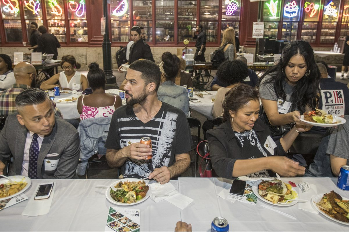 """A diverse group of diners partakes in the food prepared for the """"Breaking Bread, Breaking Barriers""""  dinner Monday night on Filbert Street, outside Reading Terminal Market."""
