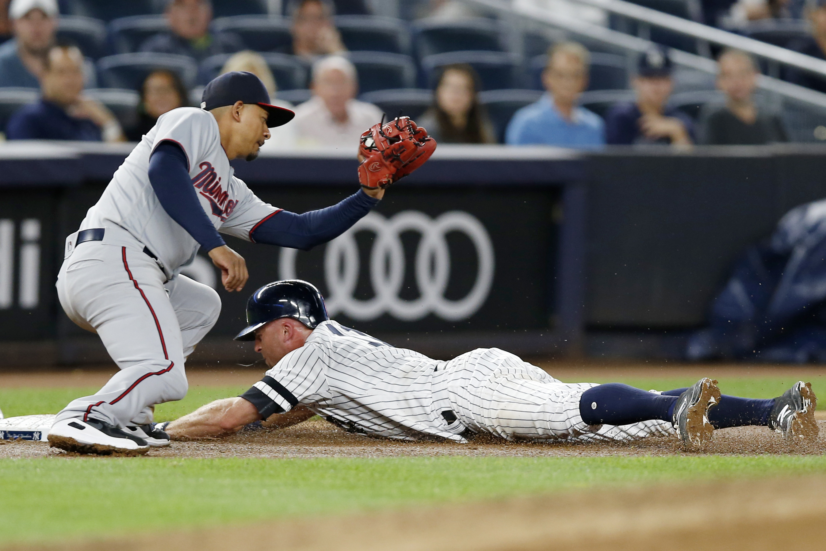 Minnesota Twins third baseman Eduardo Escobar (5) prepares to tag New York Yankees´ Brett Gardner, who is safe sliding into third on Aaron Judge´s fifth-inning flyout in a baseball game in New York, Monday, Sept. 18, 2017. (AP Photo/Kathy Willens)