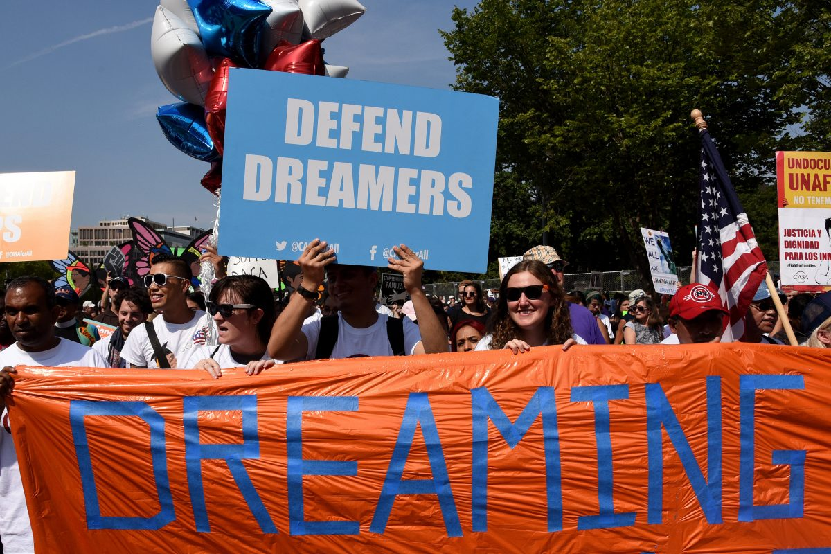 Protesters hold up signs during a rally supporting Deferred Action for Childhood Arrivals outside the White House on September 5, 2017.