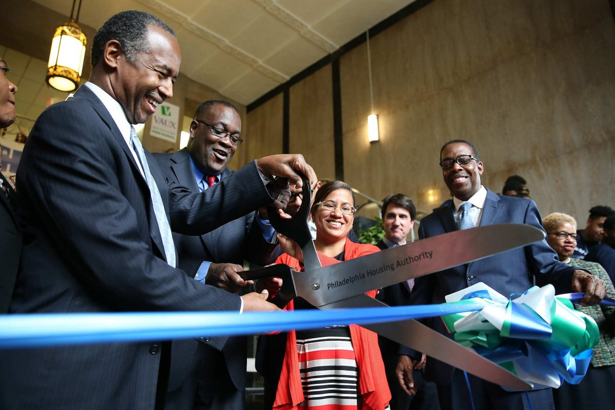 Housing and Urban Development Secretary Ben Carson (left) helps PHA president Kelvin Jeremiah (center) during the ribbon cutting at Vaux Big Picture High School in Philadelphia on Tuesday.<br />
