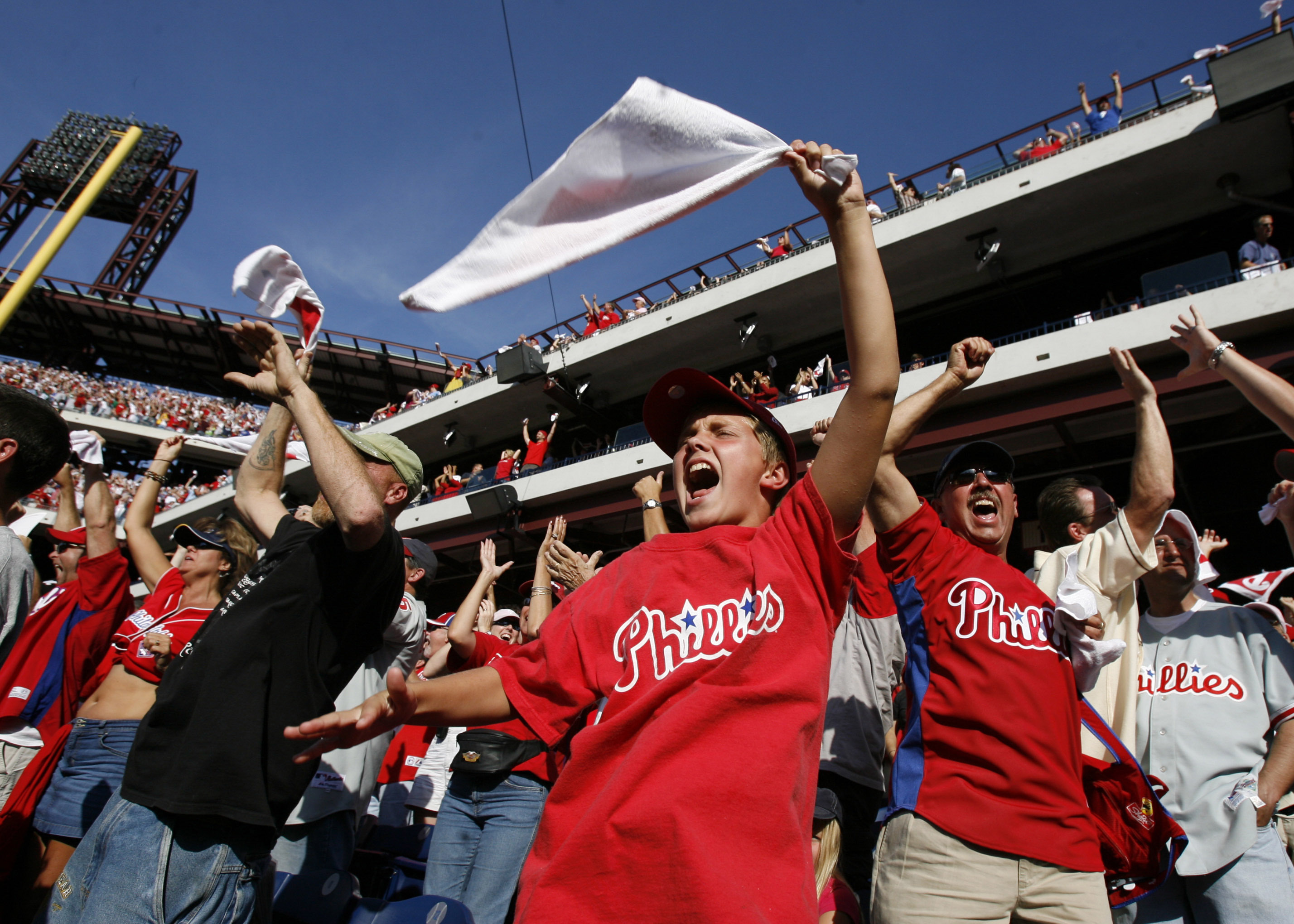 Fans celebrate as Jimmy Rollins hits a triple in the sixth inning.