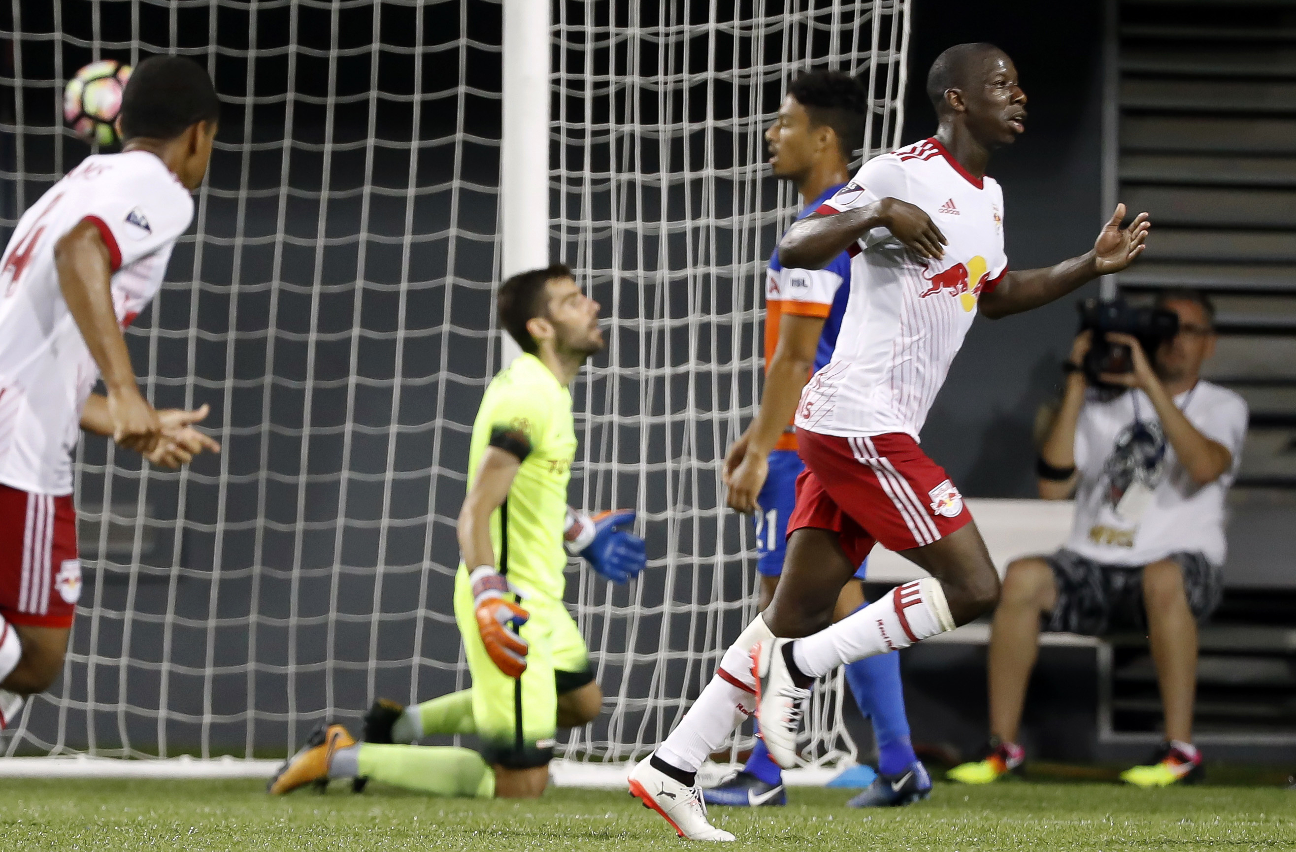 New York Red Bulls forward Bradley Wright-Phillips, right, celebrates after scoring on FC Cincinnati goalkeeper Mitch Hildebrandt, center left, in second overtime of a U.S. Open Cup soccer semi-final match Tuesday, Aug. 15, 2017, in Cincinnati. The Red Bulls won 3-2. (AP Photo/John Minchillo)