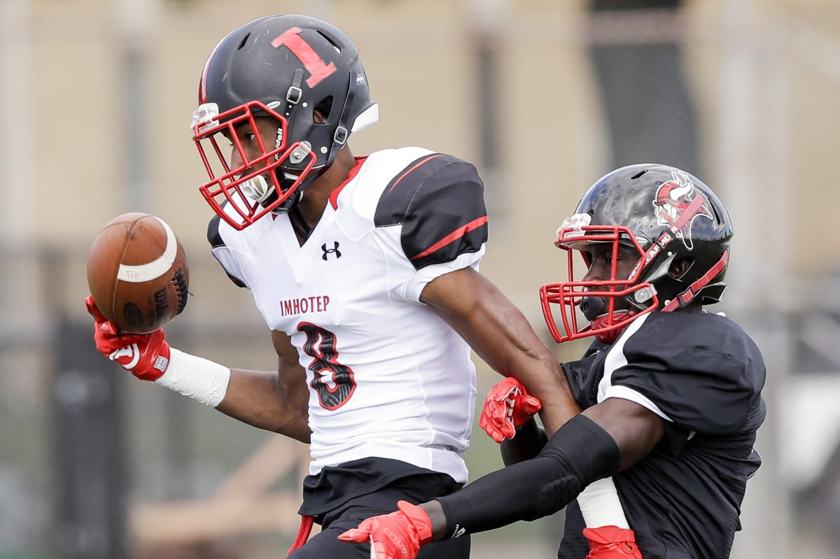 Imhotep's Yusuf Terry (left) holds off Northeast High defender Alex Martin during the teams'  game on Sept. 8. Terry scored a touchdown on the play.