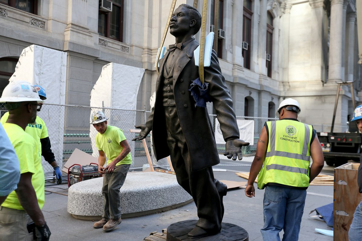 Workers install a statue of Octavius V. Catto at City Hall on Sunday.  The likeness of the 19th Century civil rights advocate is one part of a Catto monument that will be unveiled Tuesday.