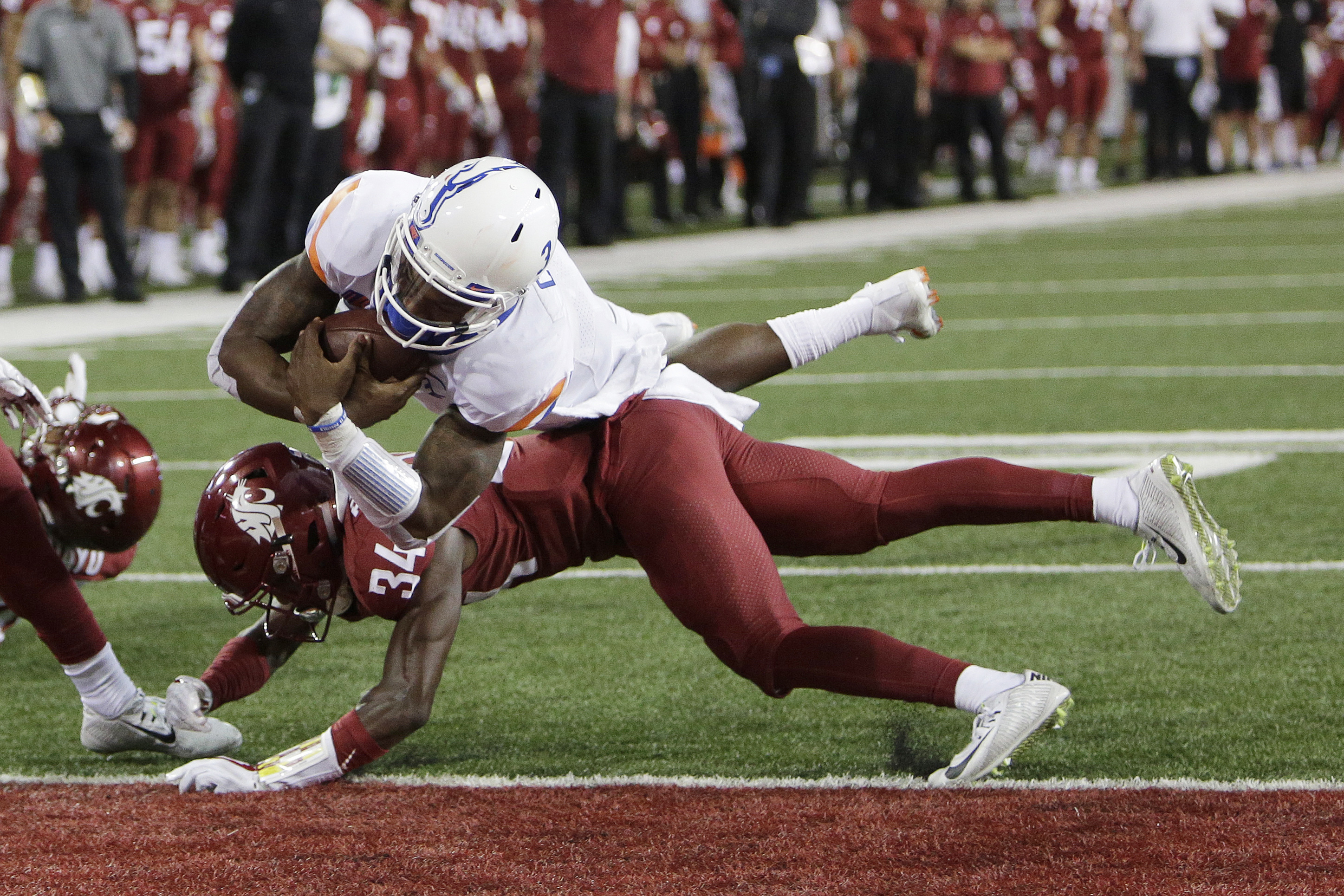 Boise State quarterback Montell Cozart, top, dives for a touchdown over Washington State safety Jalen Thompson (34) during the second half of an NCAA college football game in Pullman, Wash., Saturday, Sept. 9, 2017. Washington State won 47-44. (AP Photo/Young Kwak)