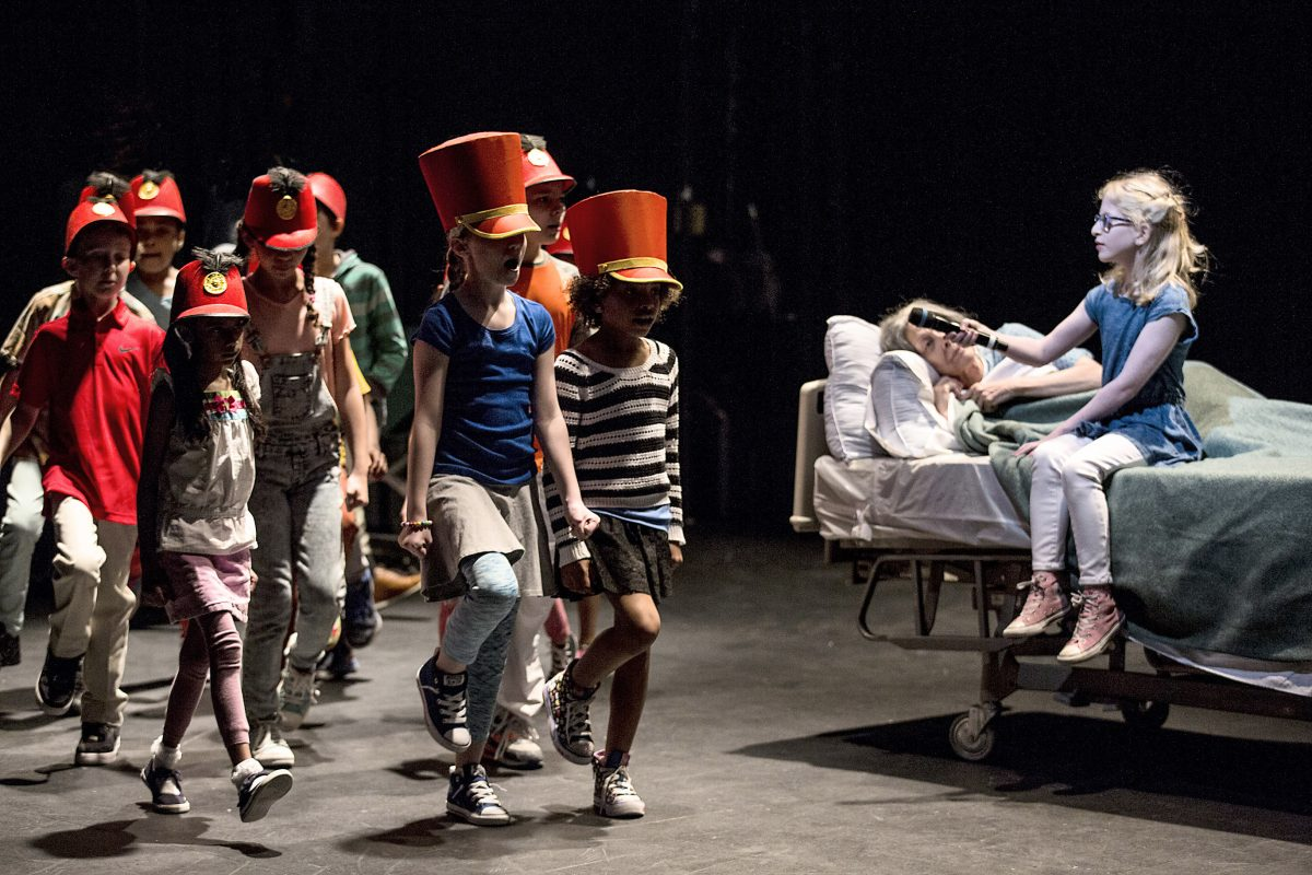 "Nancy Boykin (in bed) with Margalit Eisenstein and a children's choir in Pig Iron's ""A Period of Animate Existence."""