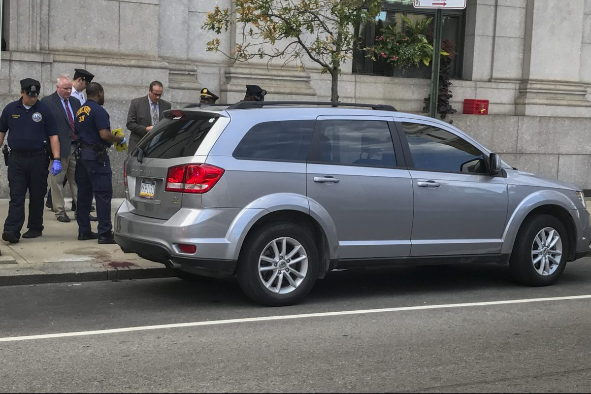 Philadelphia police crime scene officers beside the SUV in which a child accidentally shot his uncle at 16th and Arch Streets.