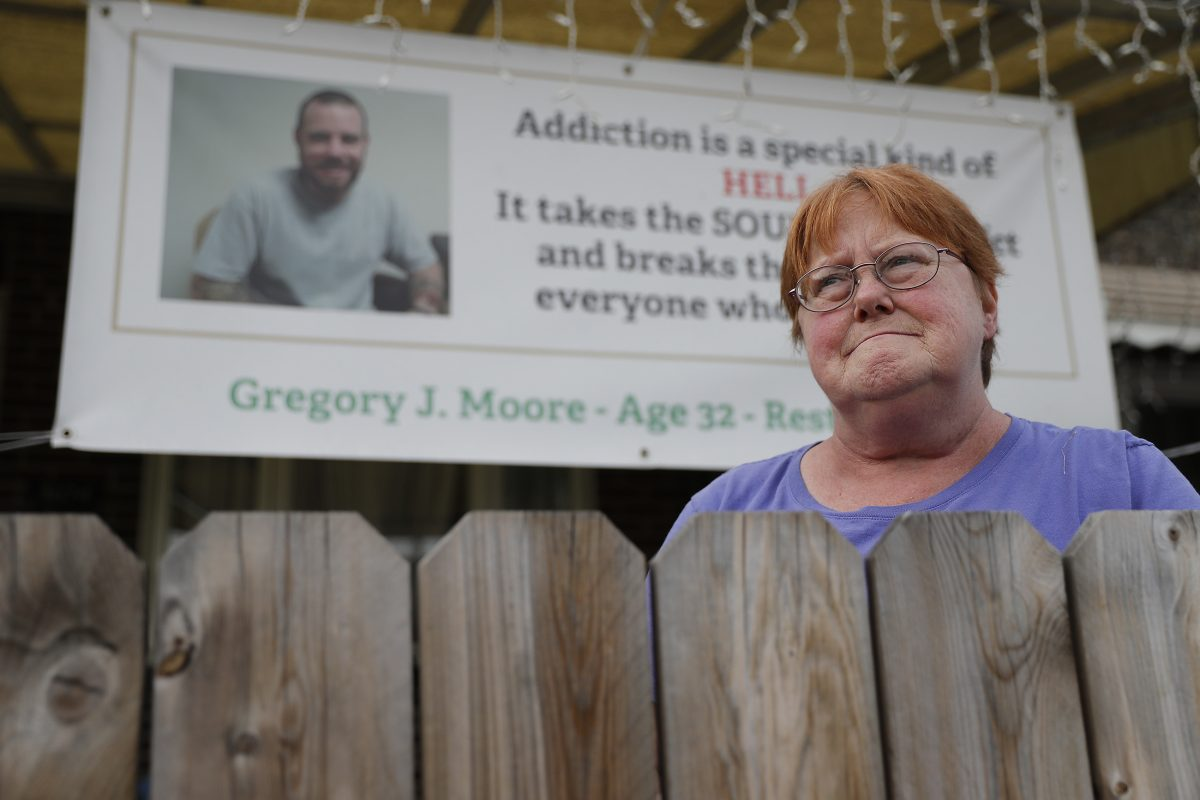 Kathleen Deacy Moore, whose son, Gregory Moore, died of a heroin overdose earlier this year, hung a banner about her son's death in front of her house.