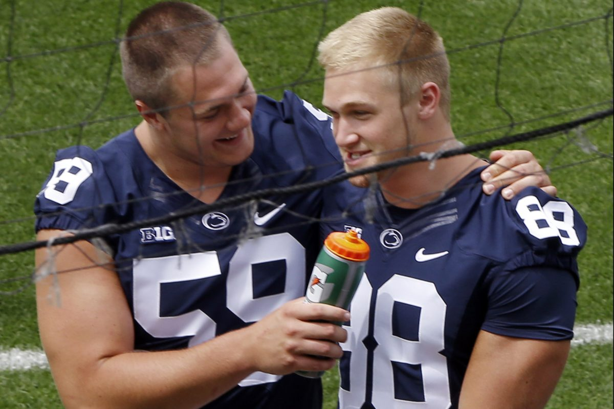 Penn State offensive tackle Andrew Nelson (left) uses a water bottle as a prop while pretending to interview tight end Mike Gesicki (88) during the Penn State's media day.