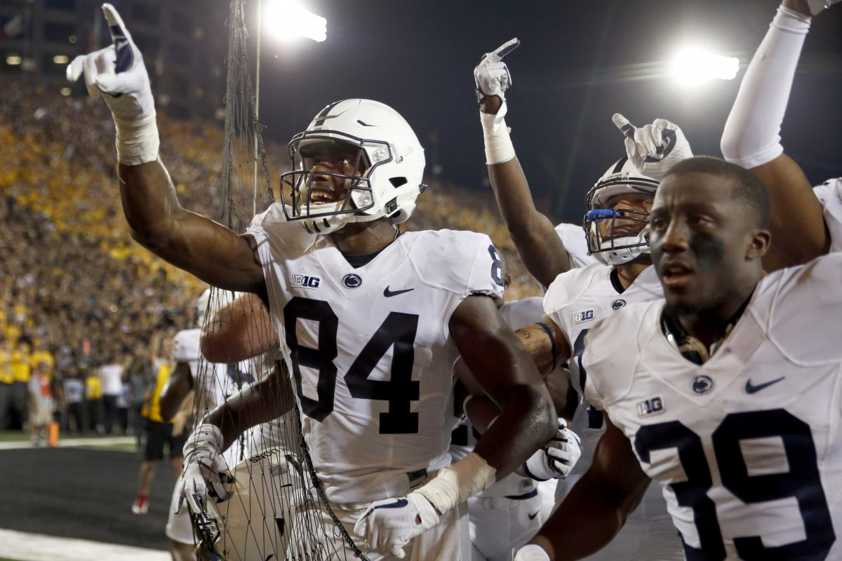 Penn State wide receiver Juwan Johnson (left) celebrates alongside teammates after catching the game-winning, walk-off touchdown pass against Iowa on the road.