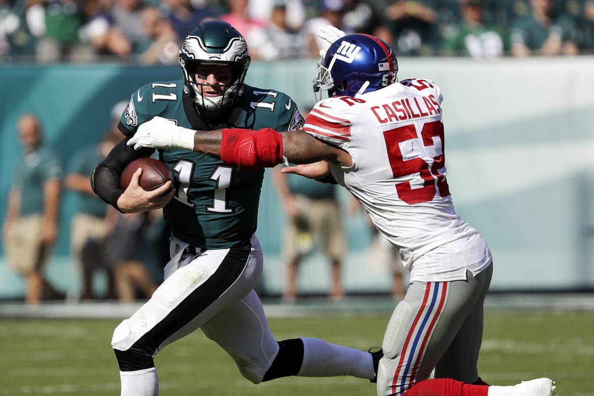 Eagles quarterback Carson Wentz runs with the football as  Giants outside linebacker Jonathan Casillas closes in.