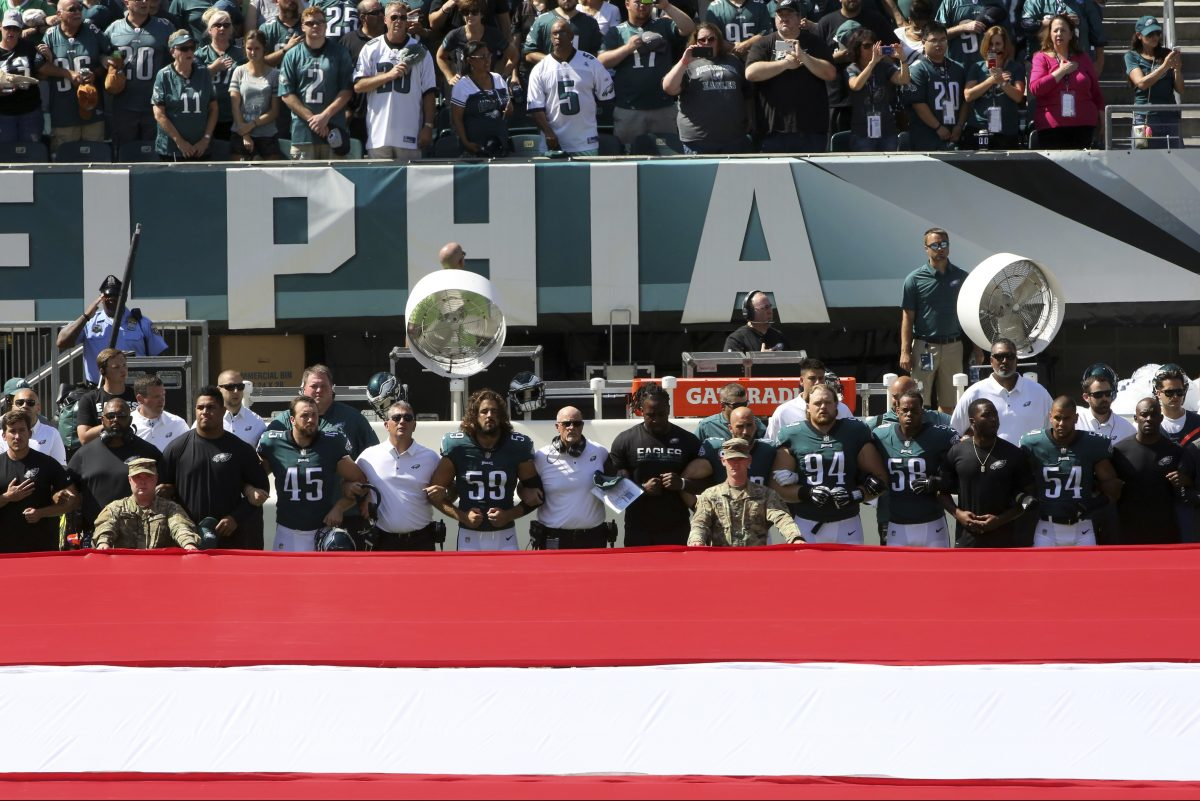 Philadelphia Eagles players and personnel stand during the national anthem before an NFL football game against the New York Giants.