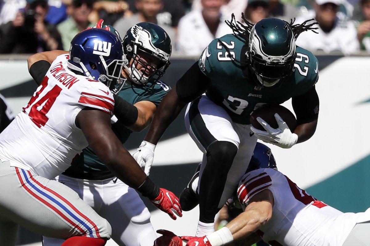 Eagles running back LeGarrette Blount leaps over New York Giants middle linebacker Calvin Munson as Eagles tight end Brent Celek blocks New York Giants defensive tackle Dalvin Tomlinson on Sunday.