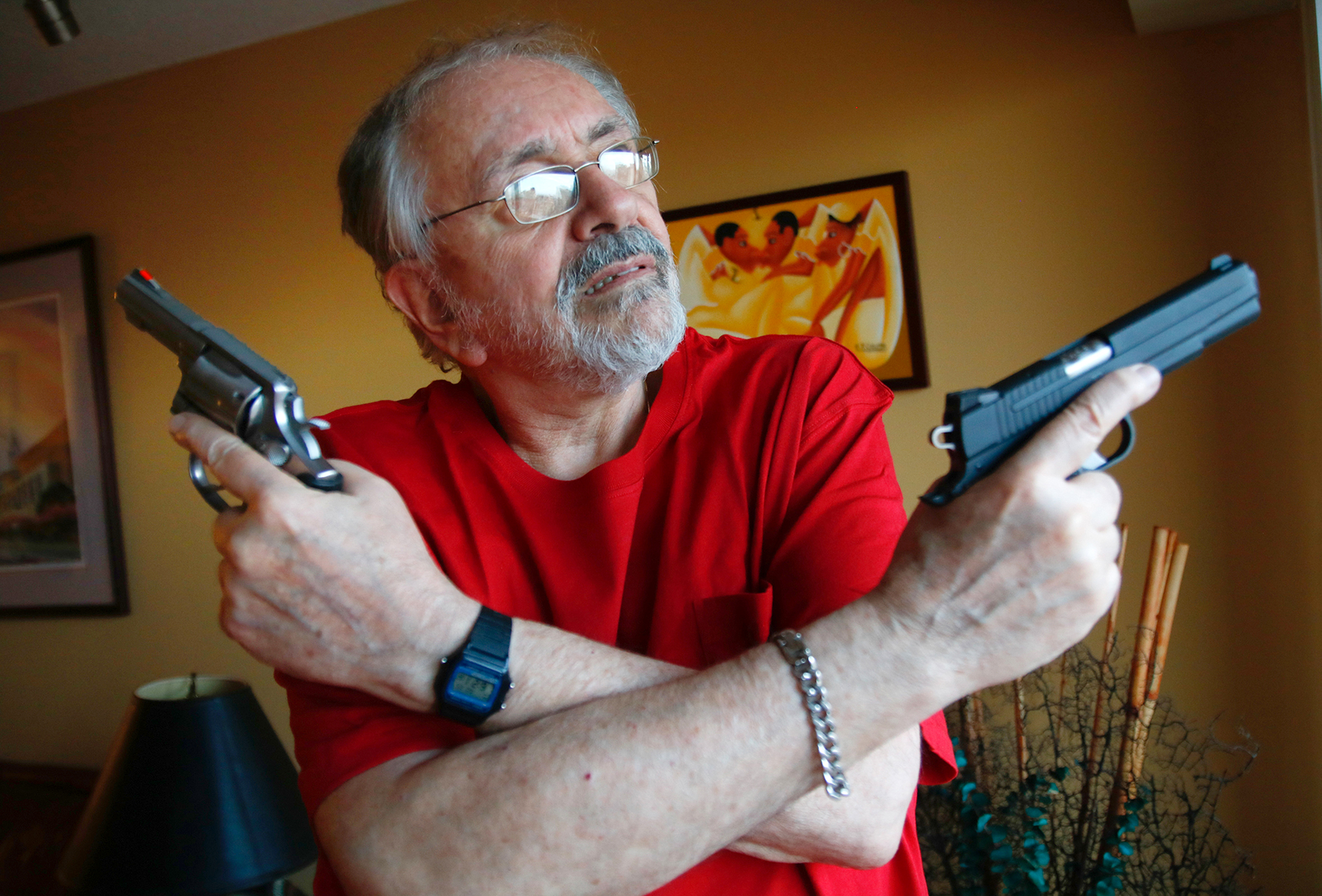 Stu Bykofsky poses in his home with two of his firearms for which he needs a gun permit.