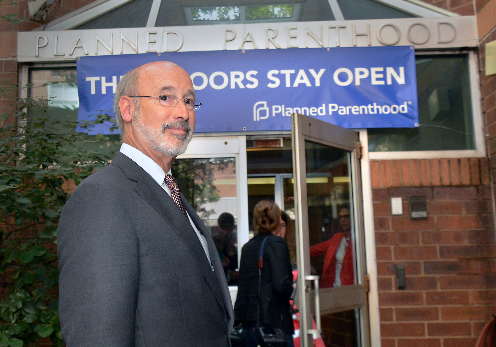 Governor Tom Wolf pauses outside of the Elizabeth Blackwell Health Center at Locust Street in Philadelphia earlier this month. Centers, schools and other county services are about to suffere from lack of a state budget.
