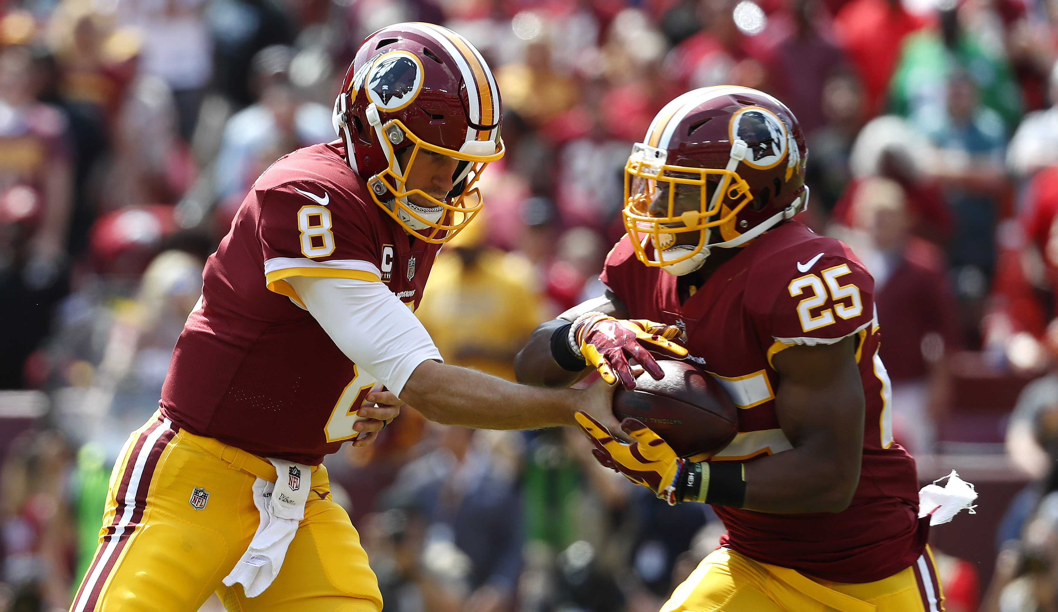 Washington Redskins quarterback Kirk Cousins, left, hands off to Washington Redskins running back Chris Thompson in the first half of an NFL football game against the Philadelphia Eagles, Sunday, Sept. 10, 2017, in Landover, Md. (AP Photo/Alex Brandon)