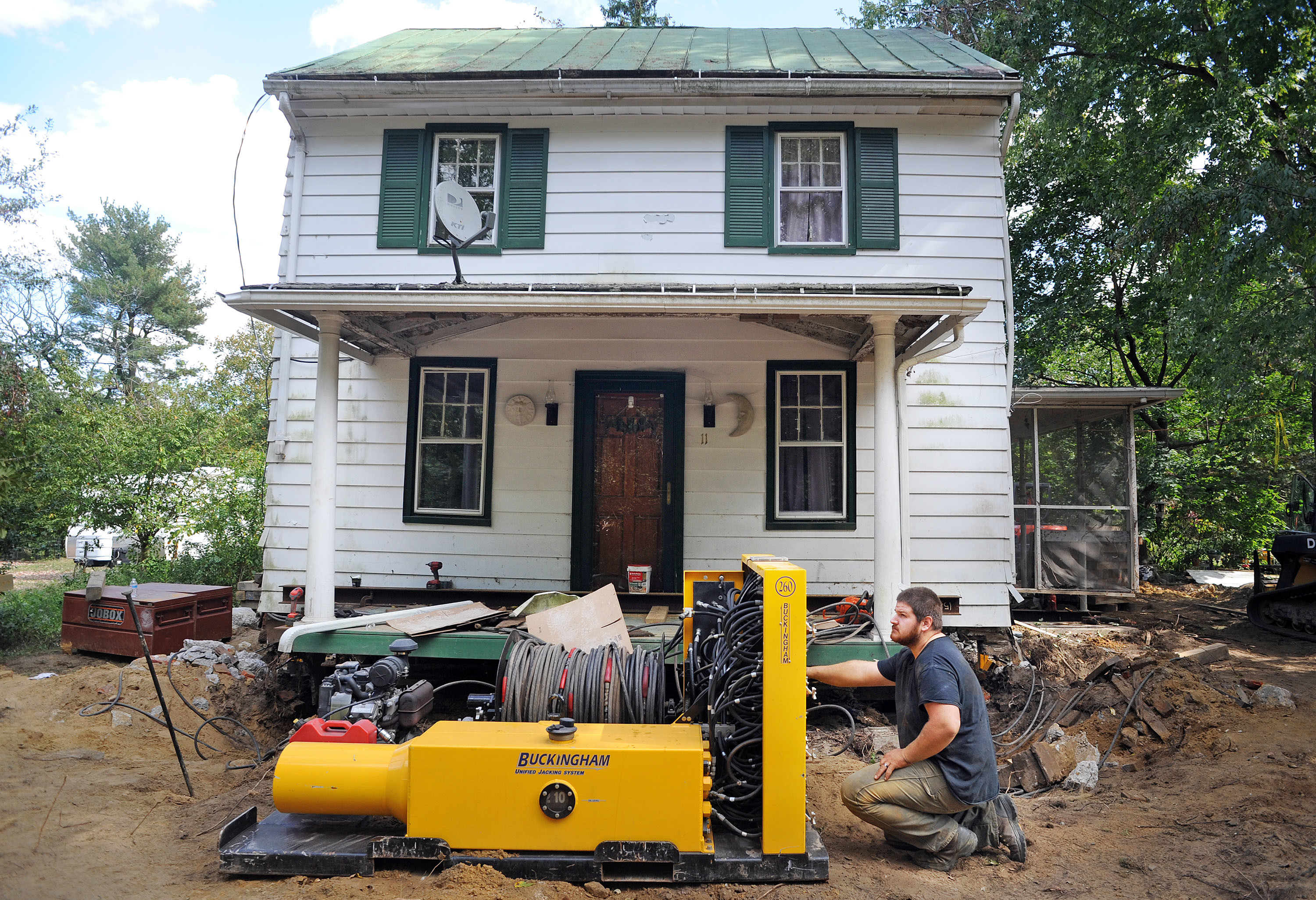 Nate Champ of Wolfe House & Building Movers works equipment Friday, Sept. 29, 2017, to raise a house on Church Street, Lumberton, NJ, to prevent future flood damage from the Rancocas Creek.