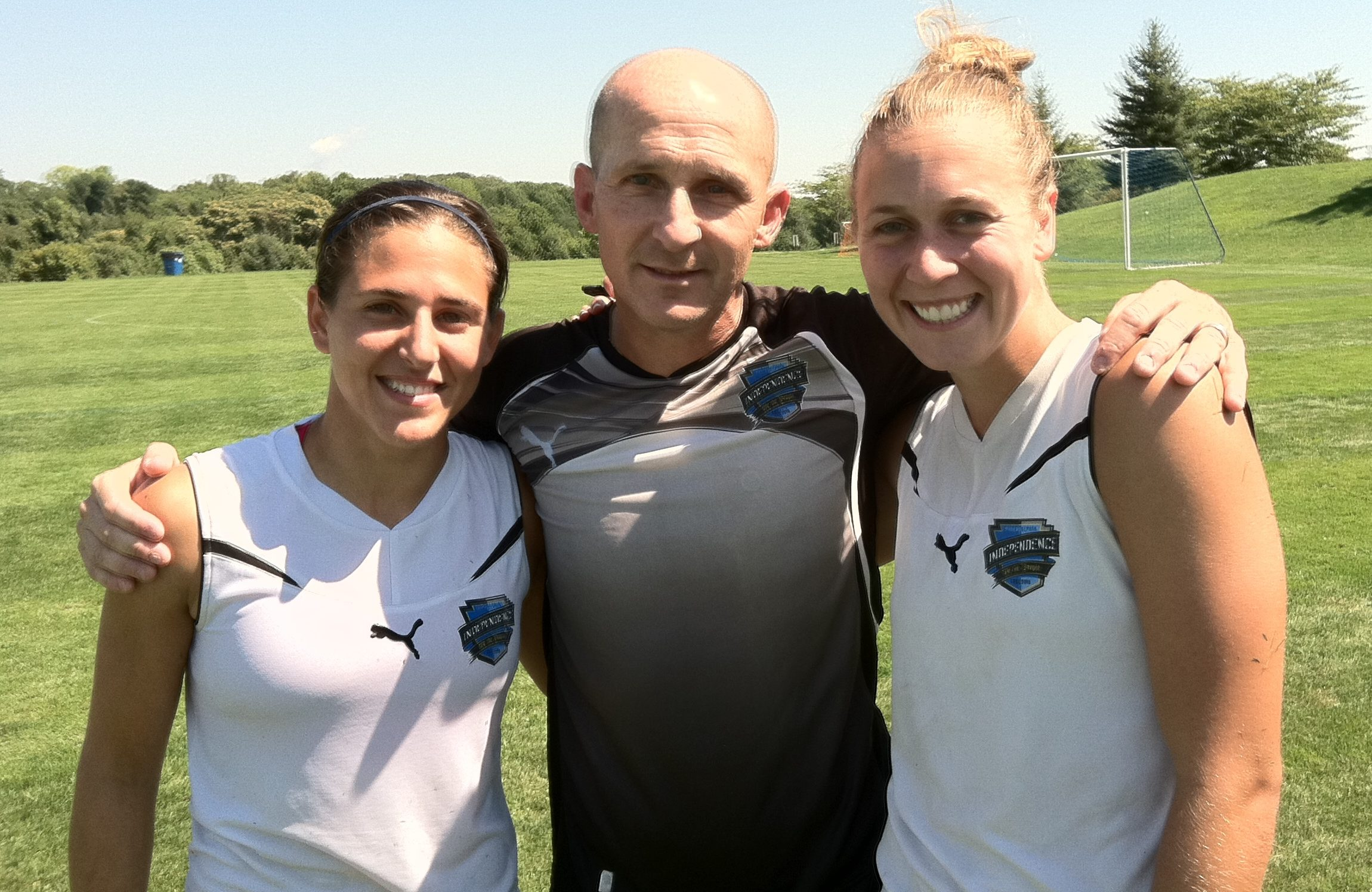Paul Riley during his days as Philadelphia Independence head coach, with players Verónica Boquete (left) and Nikki Krzysik (right).