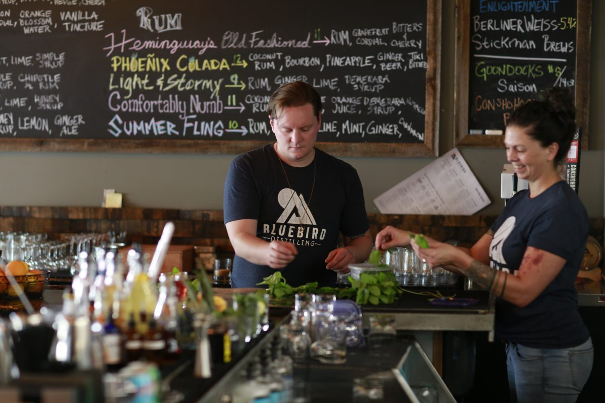 Matt Giarratano and Esther Bird pull mint off stems at Bluebird Distilling in Phoenixville.