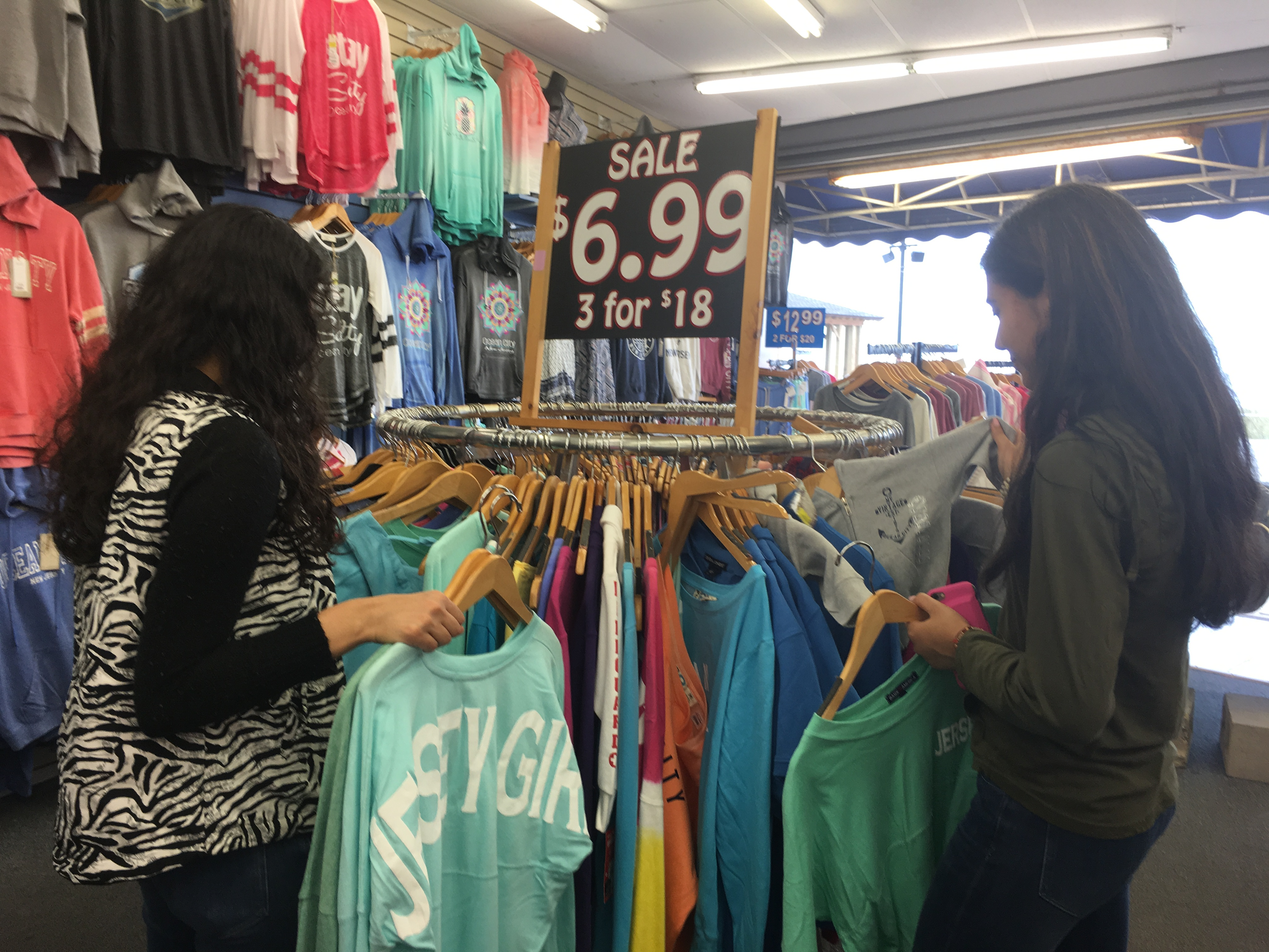 "Bargain hunters, like cousins Meg and Nina Patel of Atlantic County, leaf through sweatshirts that were ""3 for $18"" or $6.99 each, last weekend on the Ocean City boardwalk."