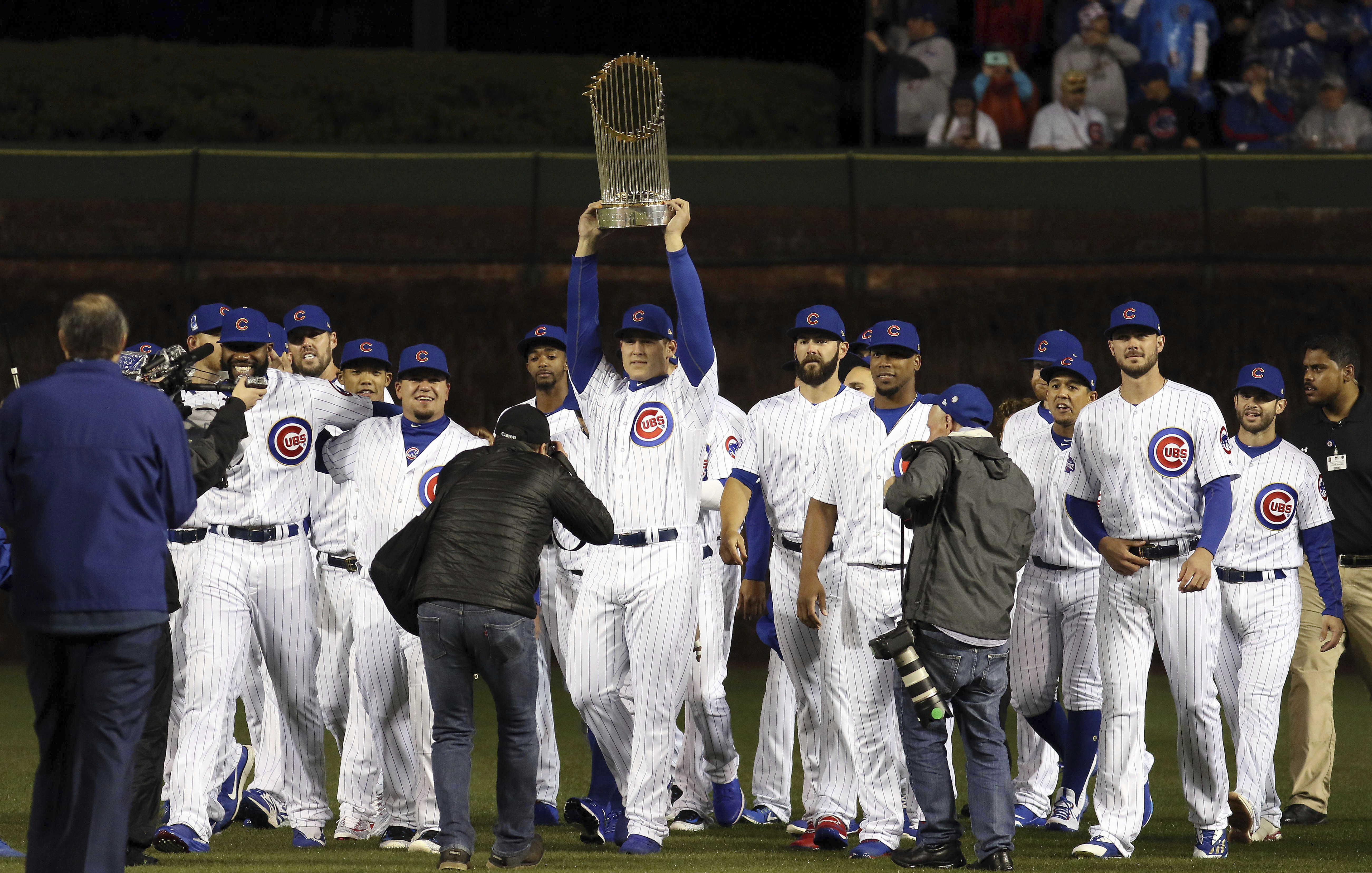 Chicago Cubs players walk the field carrying the 2016 World Series Championship trophy before a baseball game between the Chicago Cubs and the Los Angeles Dodgers on home opening day, Monday, April 10, 2017, in Chicago. (Steve Lundy/Daily Herald via AP)
