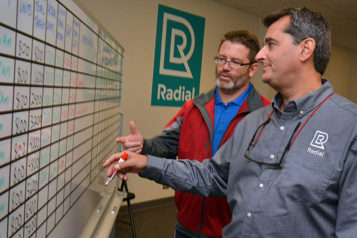 Radial HR manager Patrick Koreck (left) and  director of fulfillment operations Alex Economos go over a daily productivity board at their new fulfillment center (warehouse) in Burlington City.