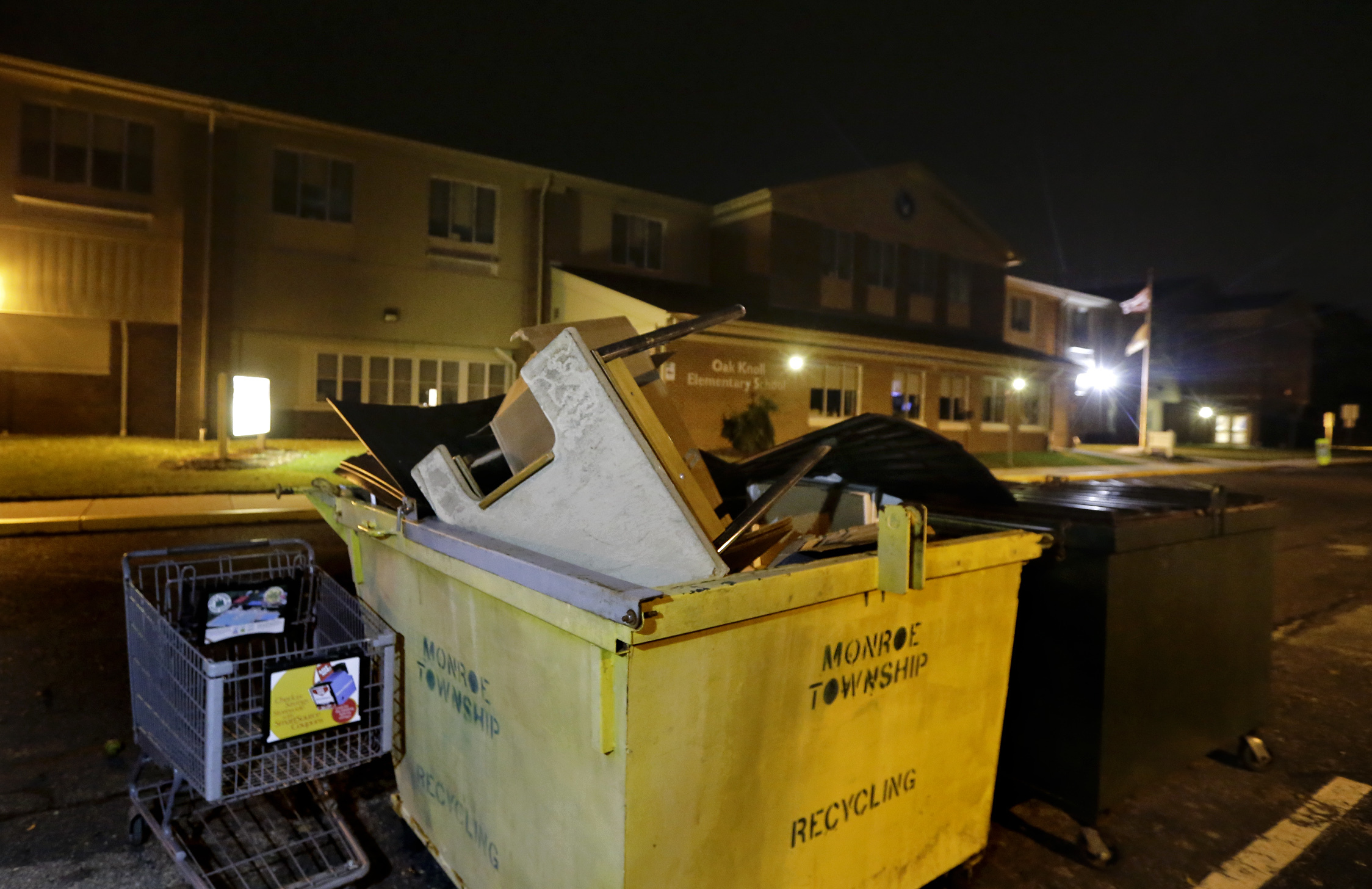 A school desk, air filters and various school related supplies in the Oak Knoll Elementary School dumpster just before 8pm on Oct. 11, 2017. Oak Knoll is one of the closed schools.
