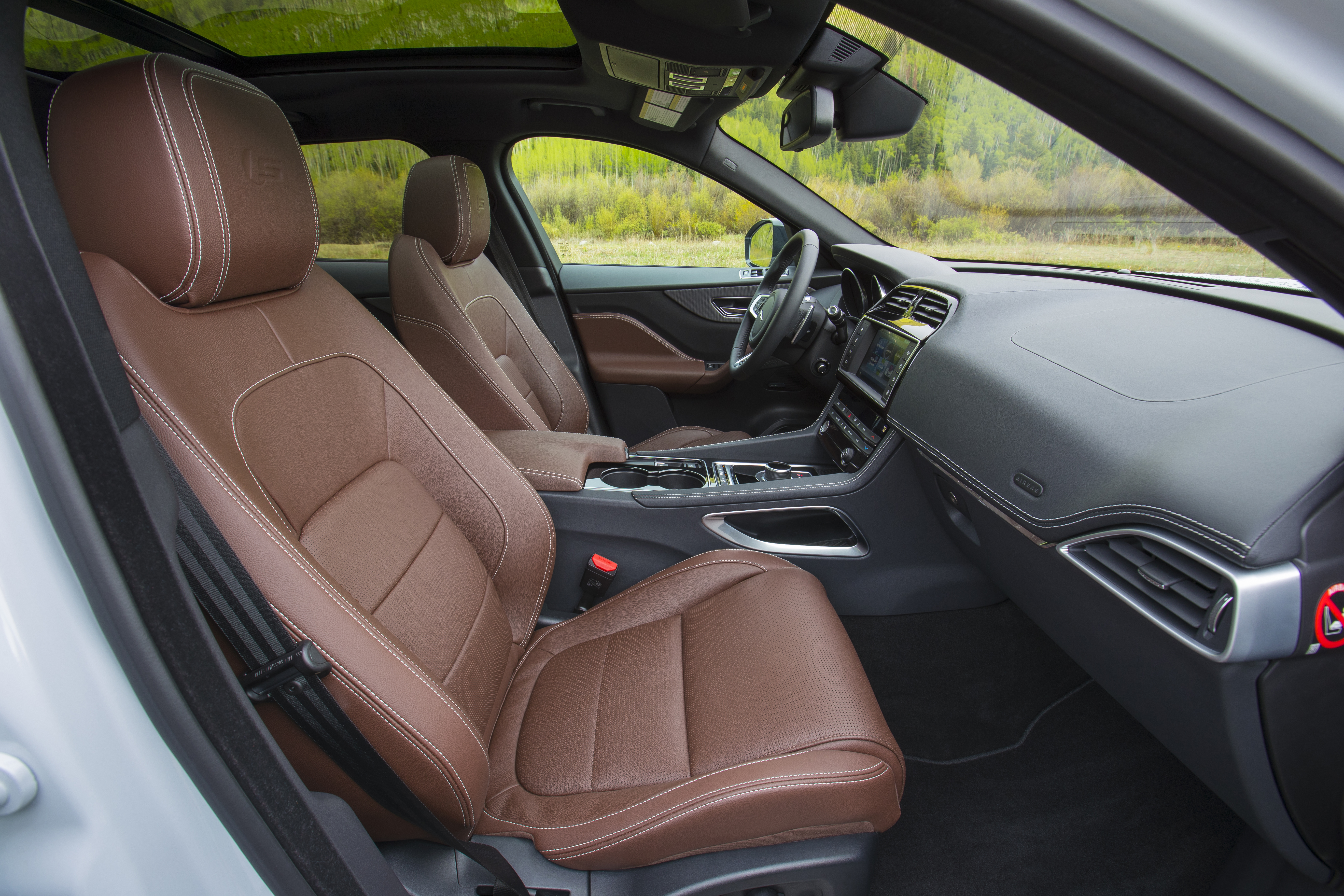 The interior of the 2017 Jaguar F Pace is certainly handsome, though the seats are firm and storage cubbies lacking.
