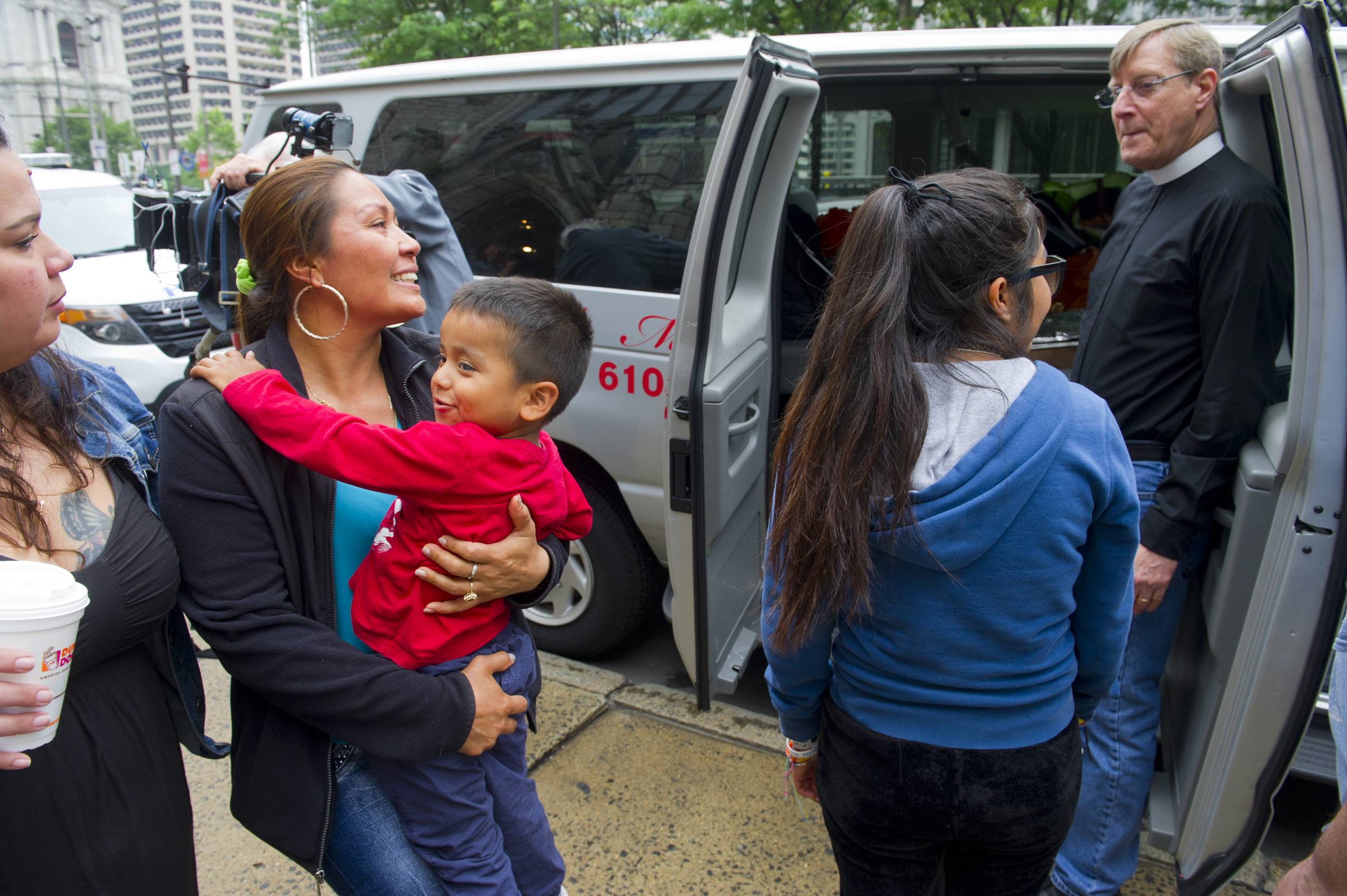 June 5, 2017 -- Alma Romero, holding her son Javier Jr., 5 and along with her daughter Adamaris, 13, and the Arch Street United Methodist Church pastor Rev. Robin Hynicka, board a van in Philadelphia Monday morning bound for New England as part of a convoy to persuade U.S. Citizenship and Immigration Services to grant her husband Javier Flores Garcia a visa for legal residency. The 40-year-old Mexican man has taken refuge at the church. (Avi Steinhardt/ For the Philadelphia Inquirer)