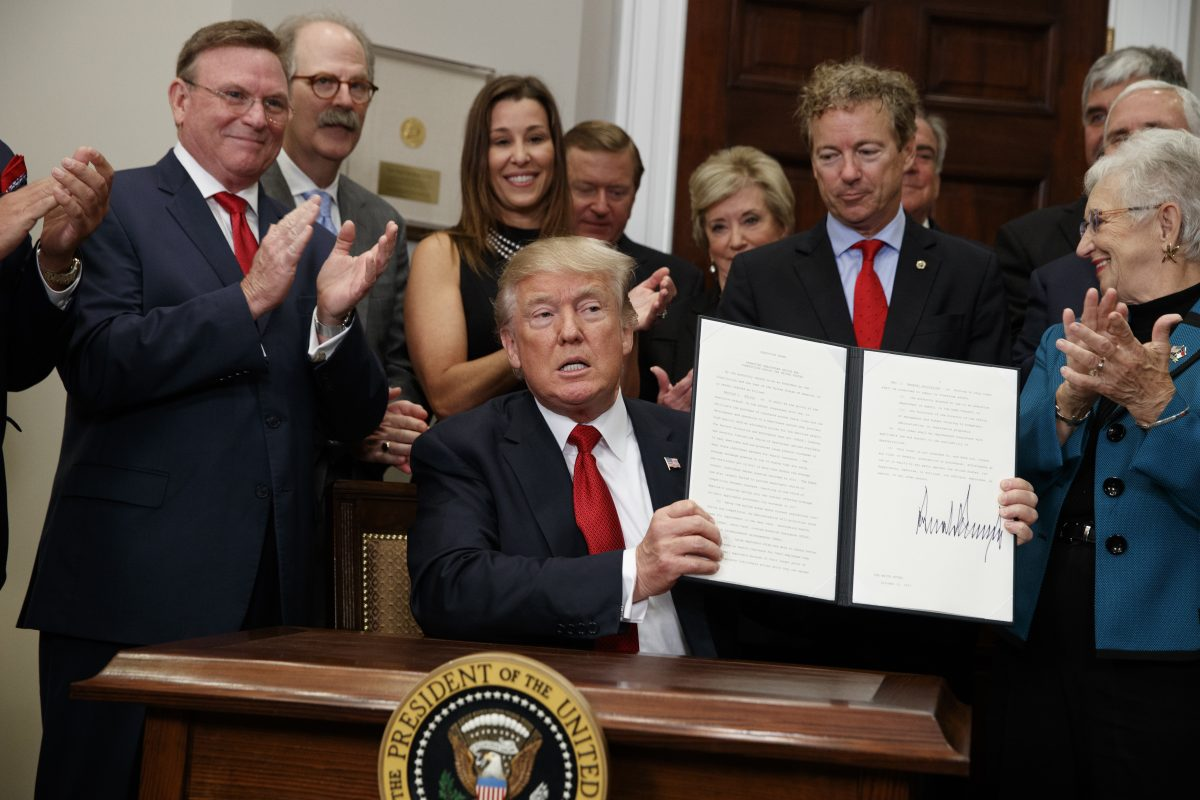 President Donald Trump shows an executive order on health care that he signed in the Roosevelt Room of the White House, Thursday, Oct. 12, 2017.