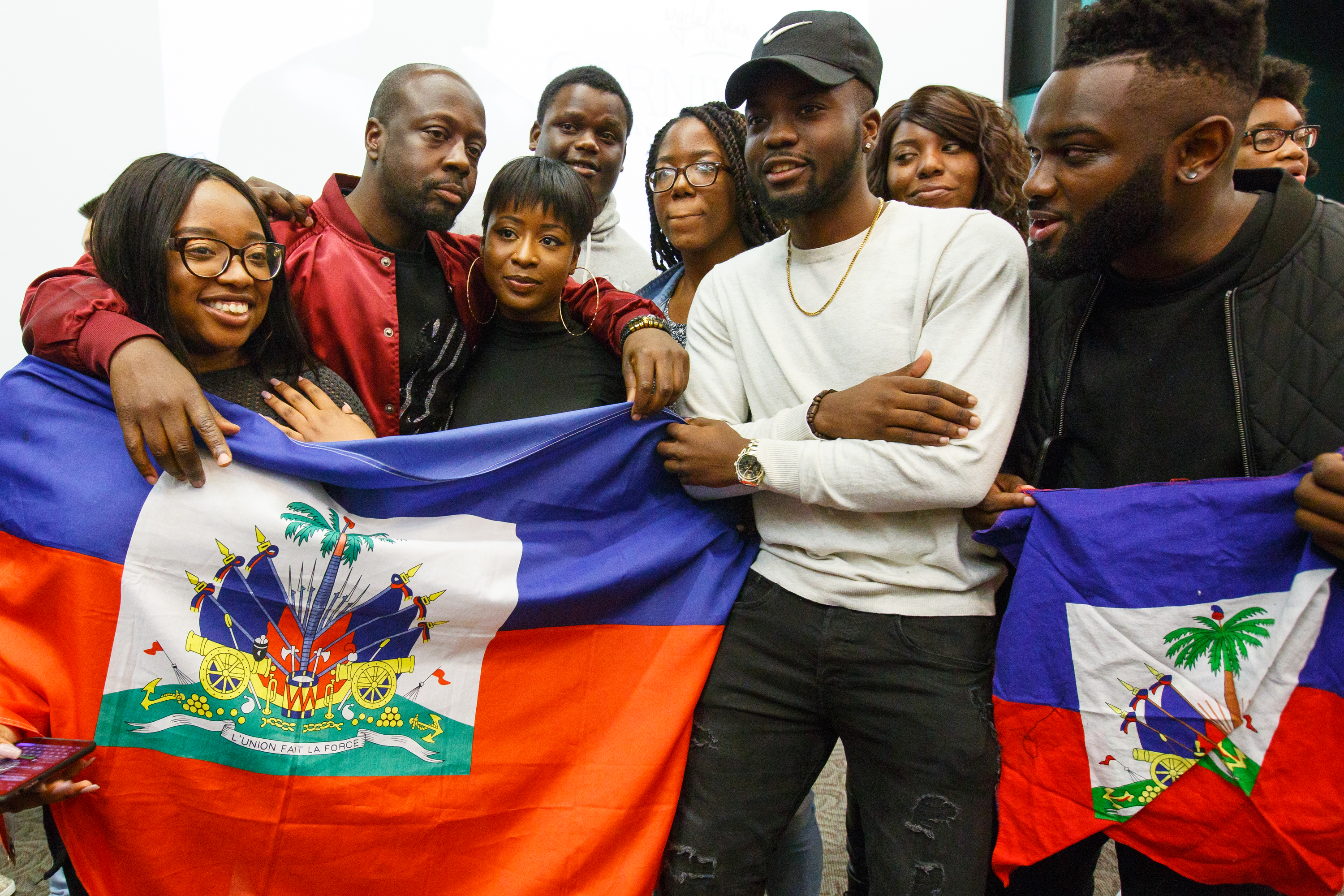 "Wcylef Jean, second from left, acclaimed hip-hop artist and producer, poses with students who brought a hatian flag to class after Wyclef spoke during a ""Hip Hop and Black Culture"" class at Temple University,"
