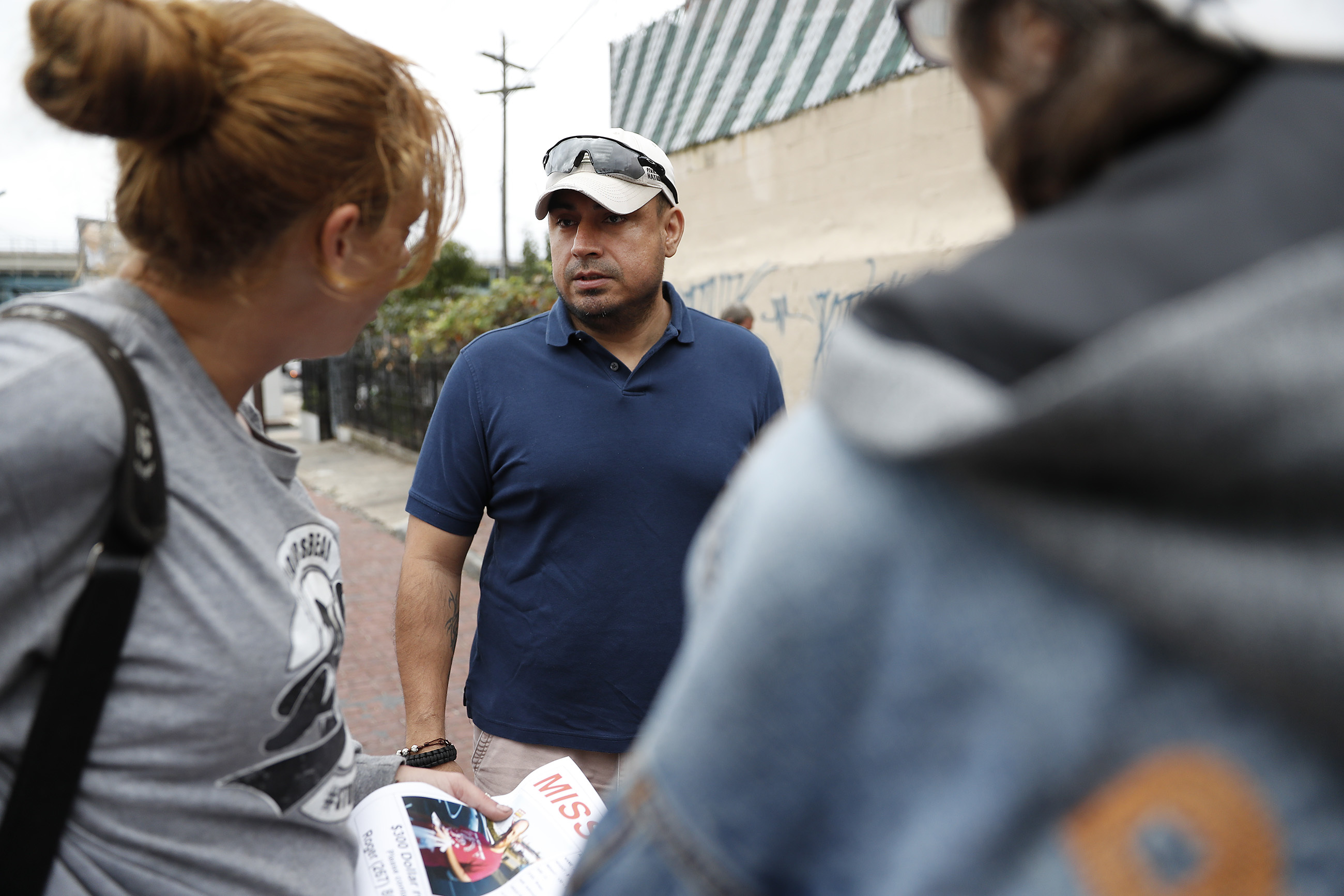 Private investigator Roger Guerra, center, talks to a group about a missing person he is looking for in the Kensington section in Philadelphia, PA on October 12, 2017.