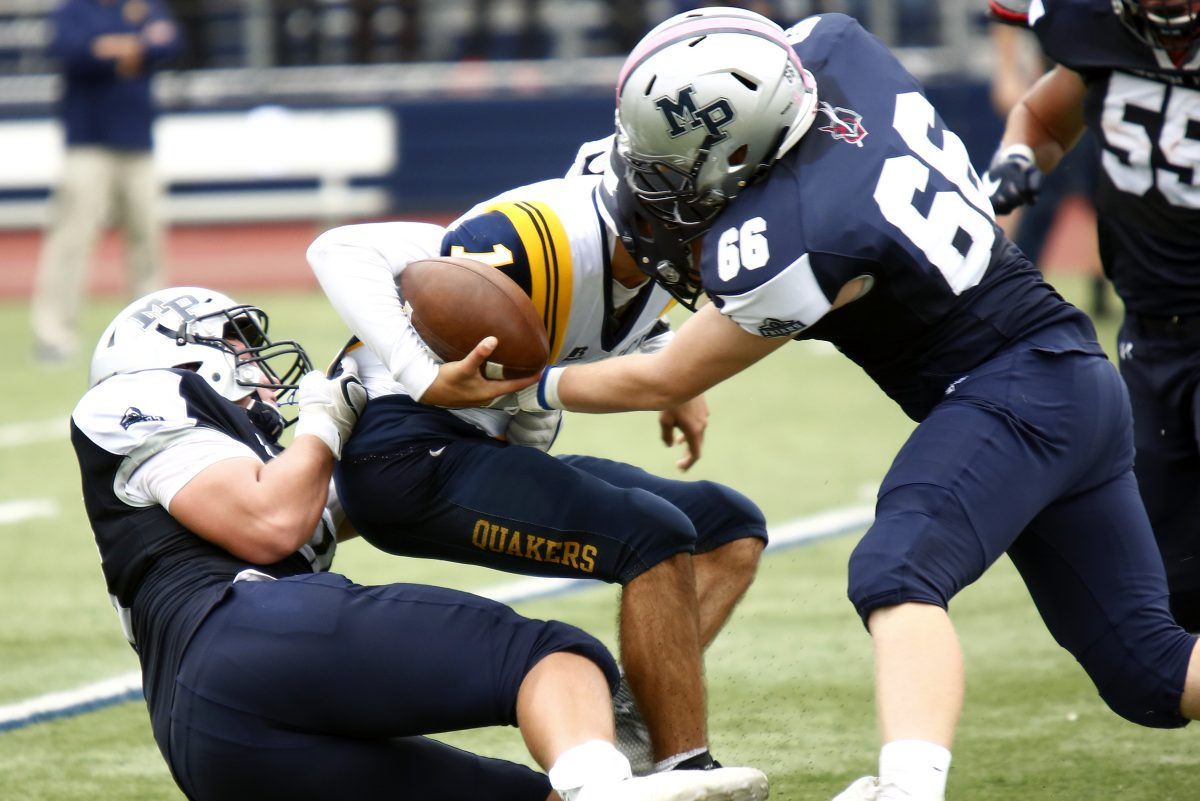 Malvern Prep defensive players Ryan Betz (left) and Jack Walker (right) combine to sack Penn Charter's Will Samuel in the fourth quarter.