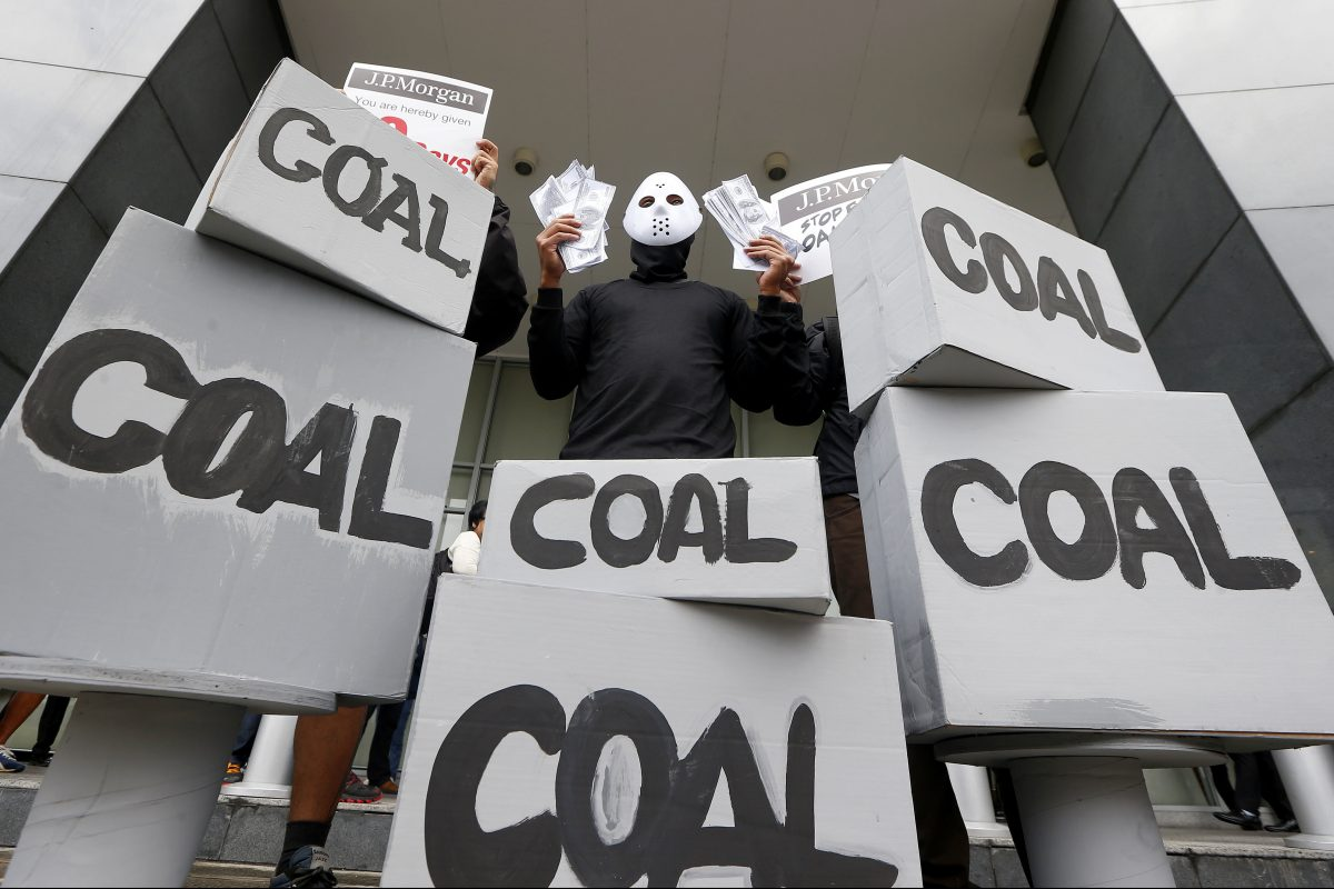An activist wags mock dollars bills during a recent protest against coal-fired power plants.