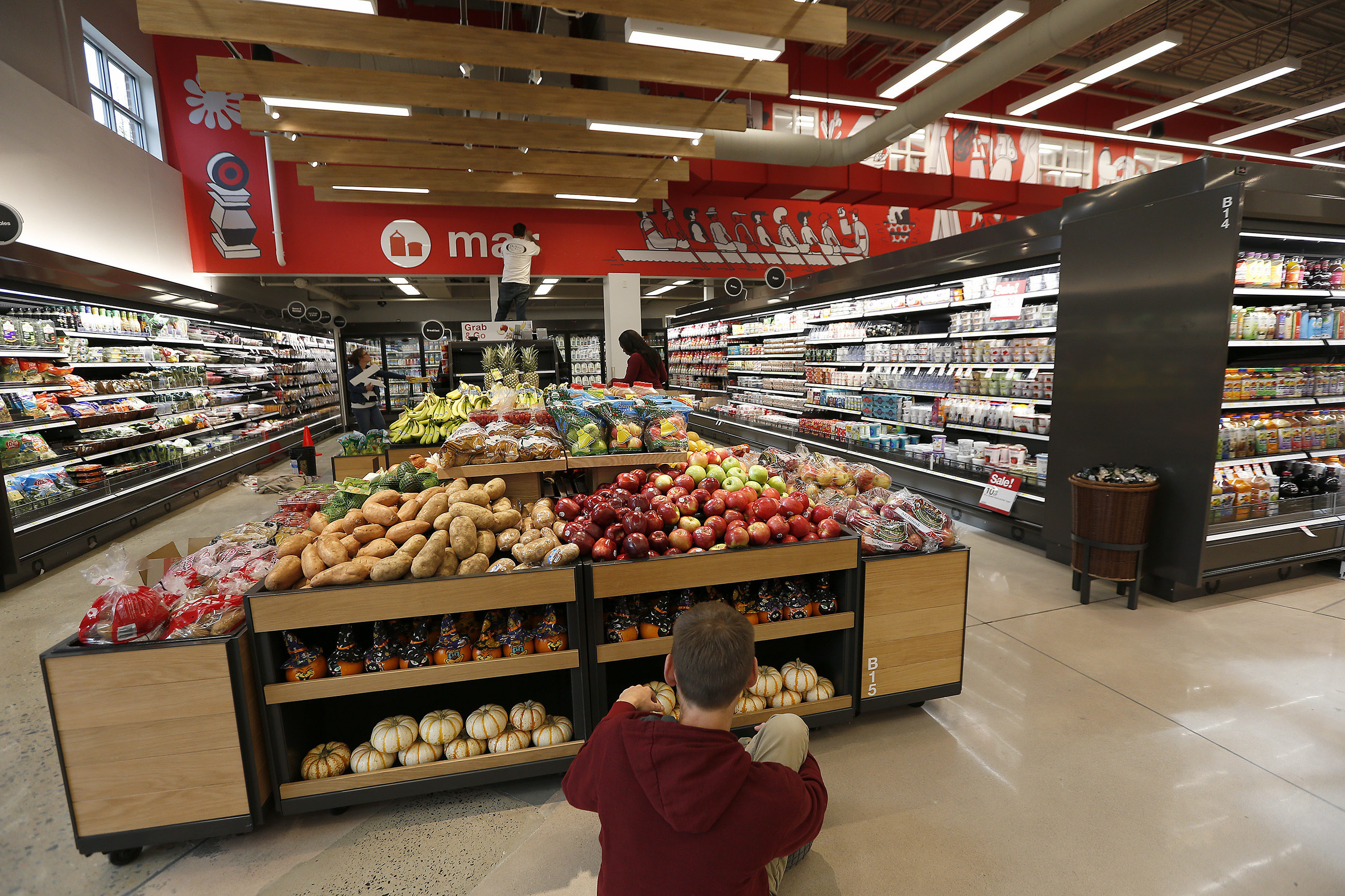 An employee stocks produce inside the new smaller format Target store in the Art Museum area that opens to the public this Wednesday at 7 a.m.