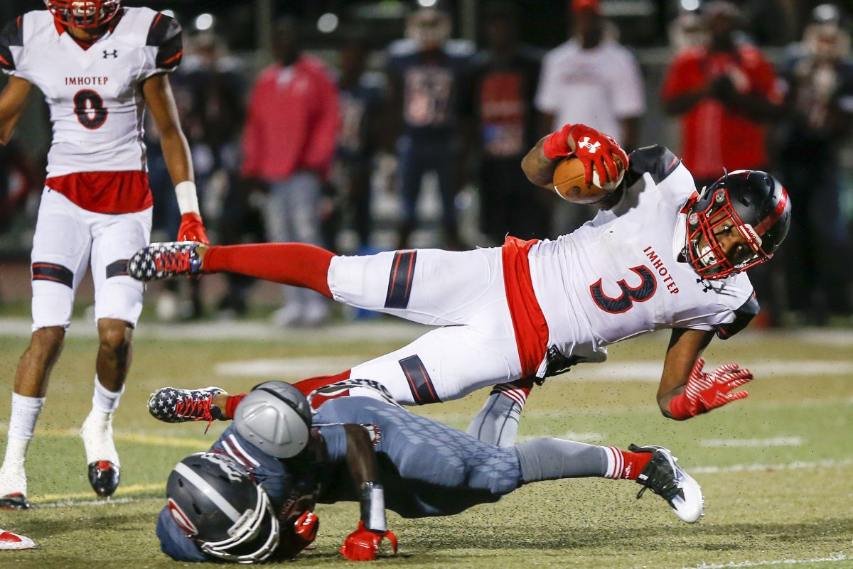 Imhotep's Isheem Young  dives for a first down against Gratz's Tarell Stewart.