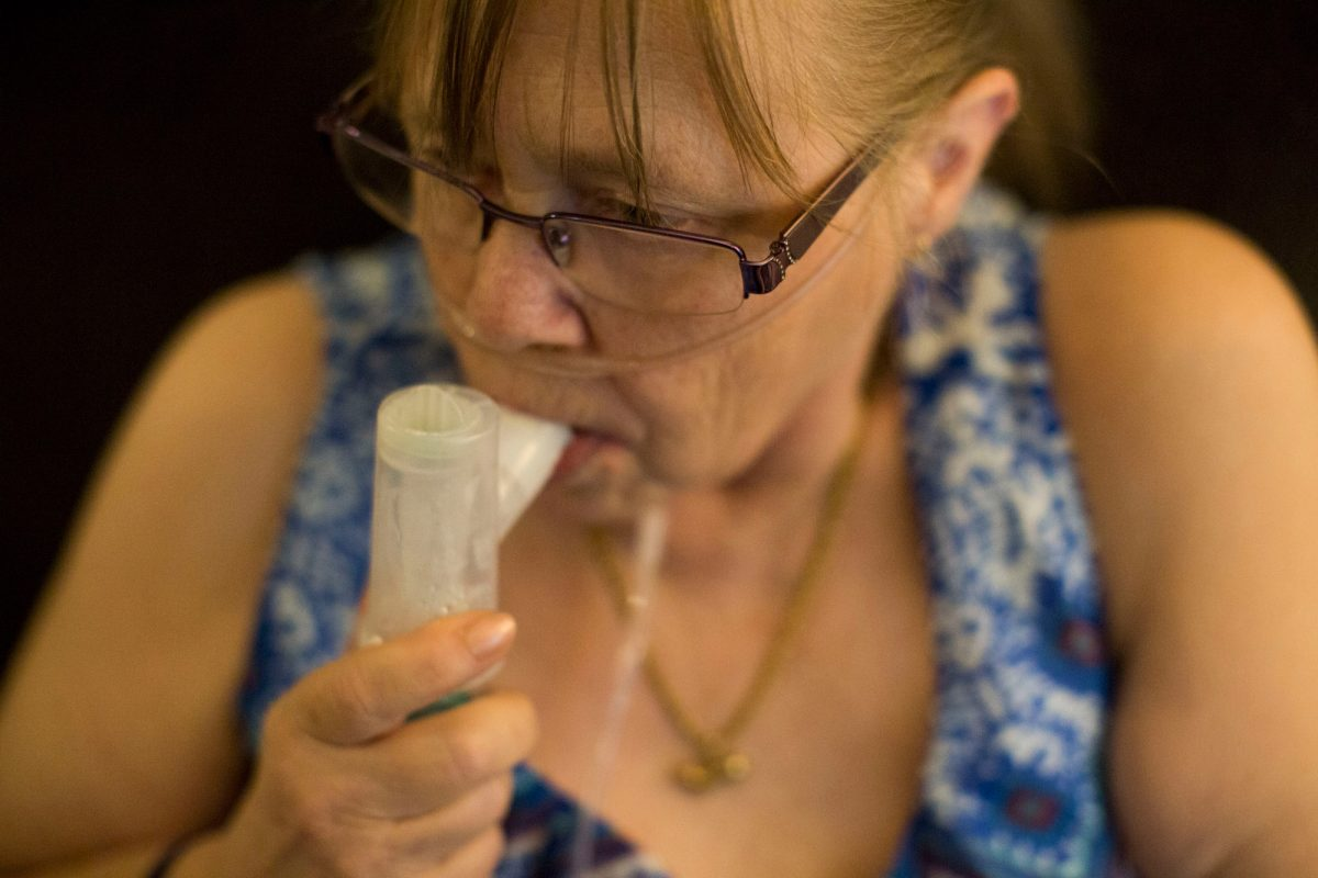 "Juanita Milton, who suffers from COPD, uses her nebulizer with albuterol sulfate at her home in Live Oak, Texas, on April 25, 2017. ""Having COPD feels like drowning,"" Milton said. (Carolyn Van Houten for Kaiser Health News)"