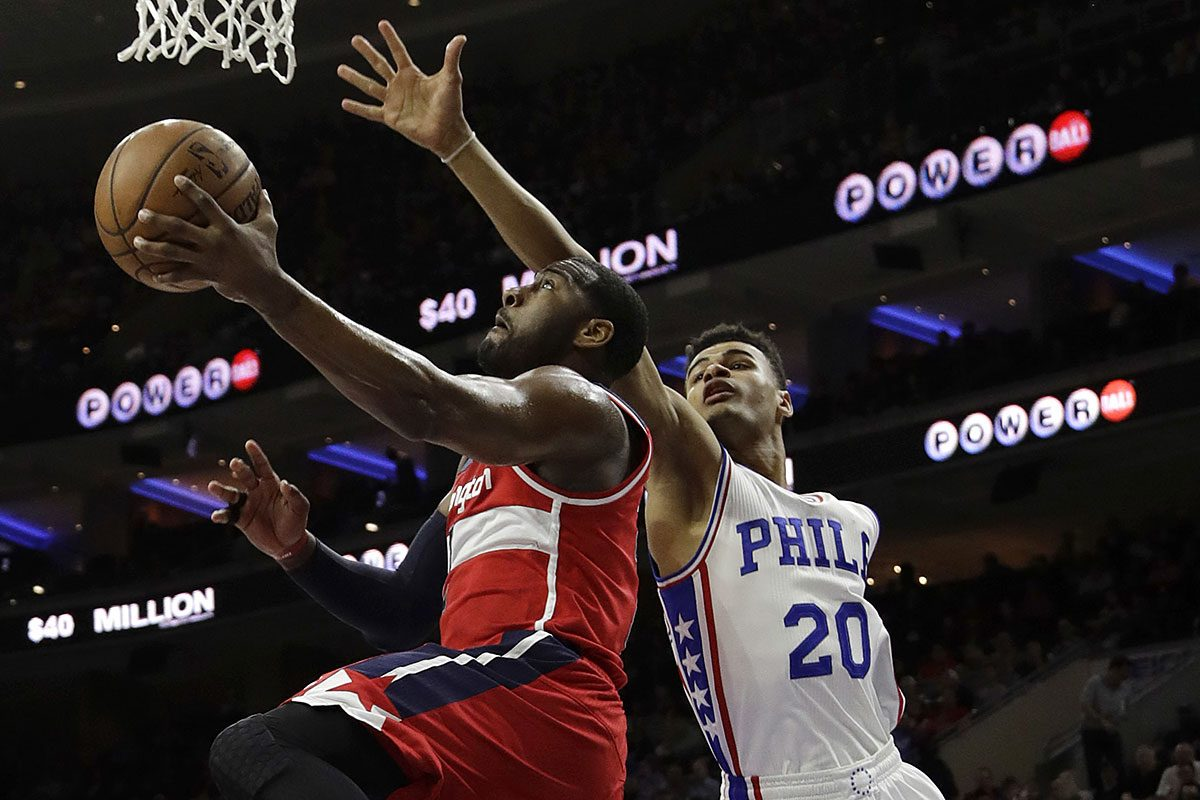 Washington Wizards' John Wall, left, goes up to shoot against Philadelphia 76ers' Timothe Luwawu-Cabarrot during the first half of an NBA basketball game, Friday, Feb. 24, 2017, in Philadelphia.