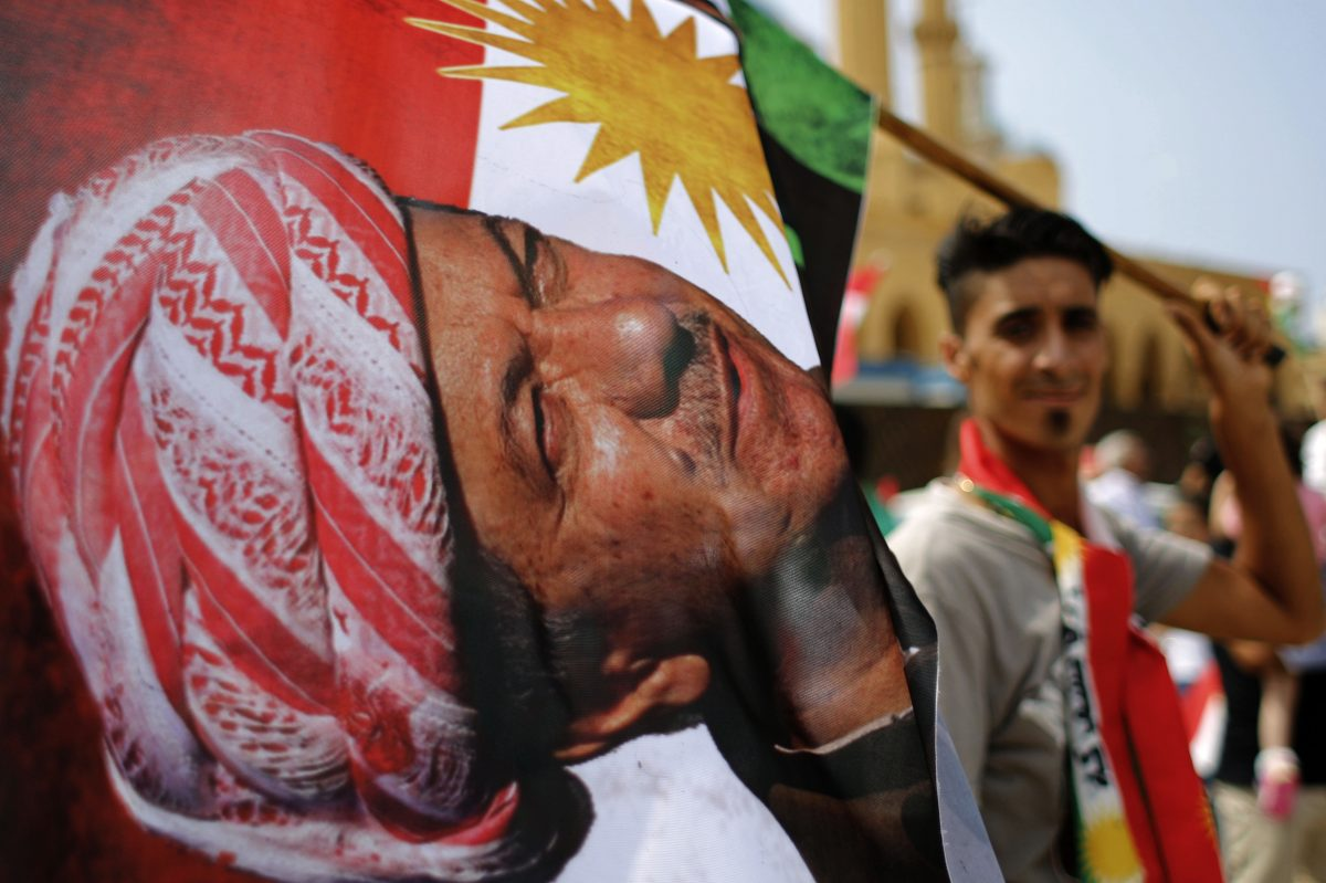In Beirut, a man holds a Kurdish flag with a picture of Iraqi Kurdish leader Masoud Barzani during a gathering to support last month's referendum.