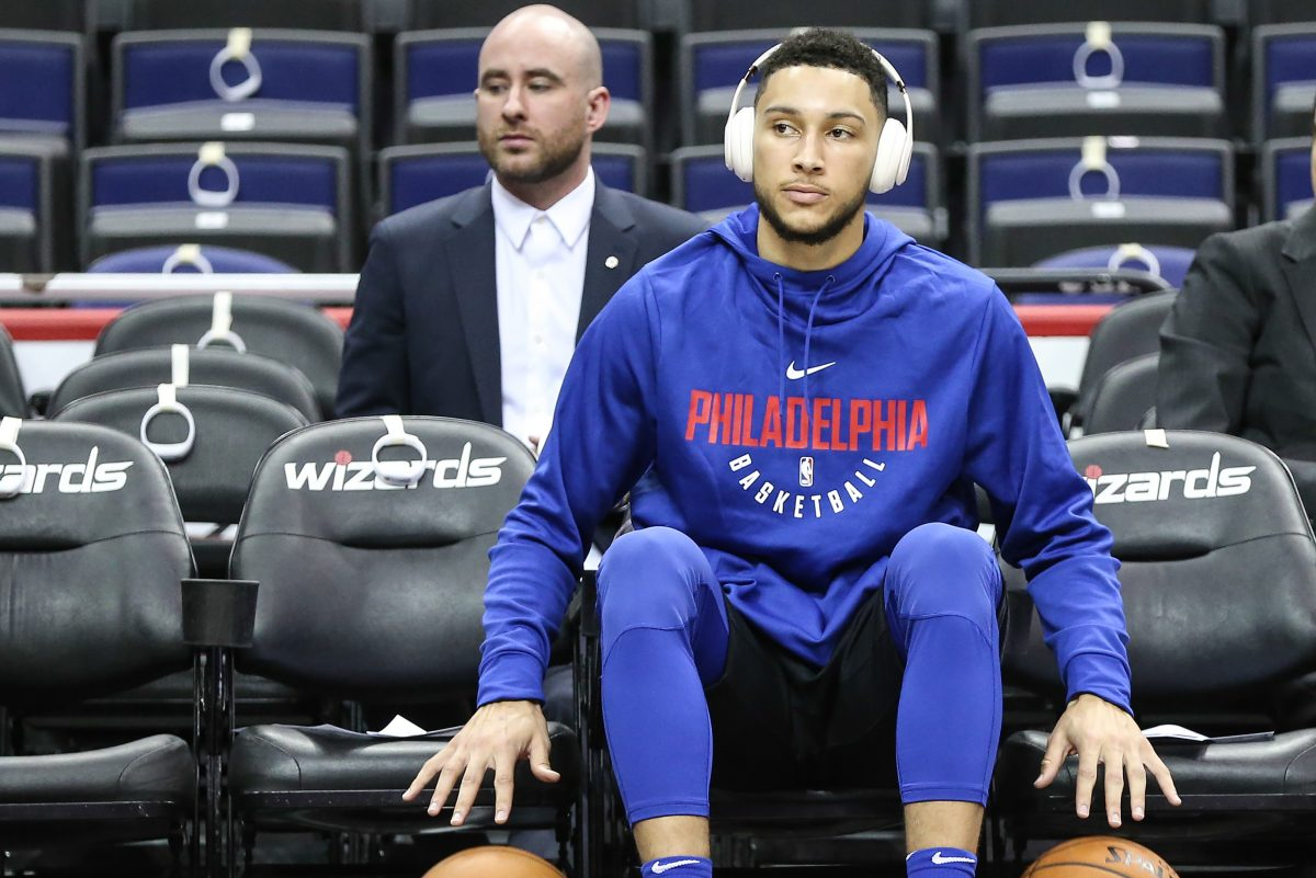 Sixers point guard Ben Simmons watches warm-ups before making his regular season NBA debut.