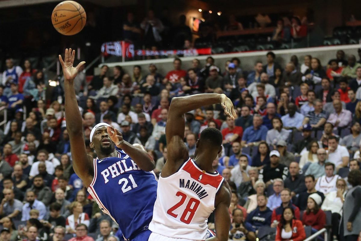 Sixers center Joel Embiid shoots over Wizards' Ian Mahinmi during the first quarter at the Capital One Arena in Washington, DC on Wednesday.