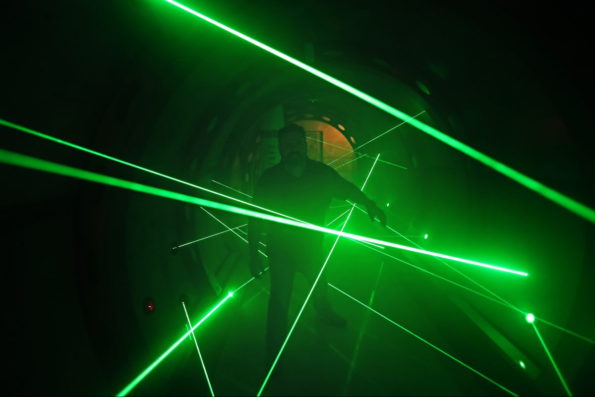 Frank Cerio, director of operations at 5 Wits, walks through lasers in a maze. The high-adventure concept debuted at Plymouth Meeting Mall on Thursday, Oct. 19.