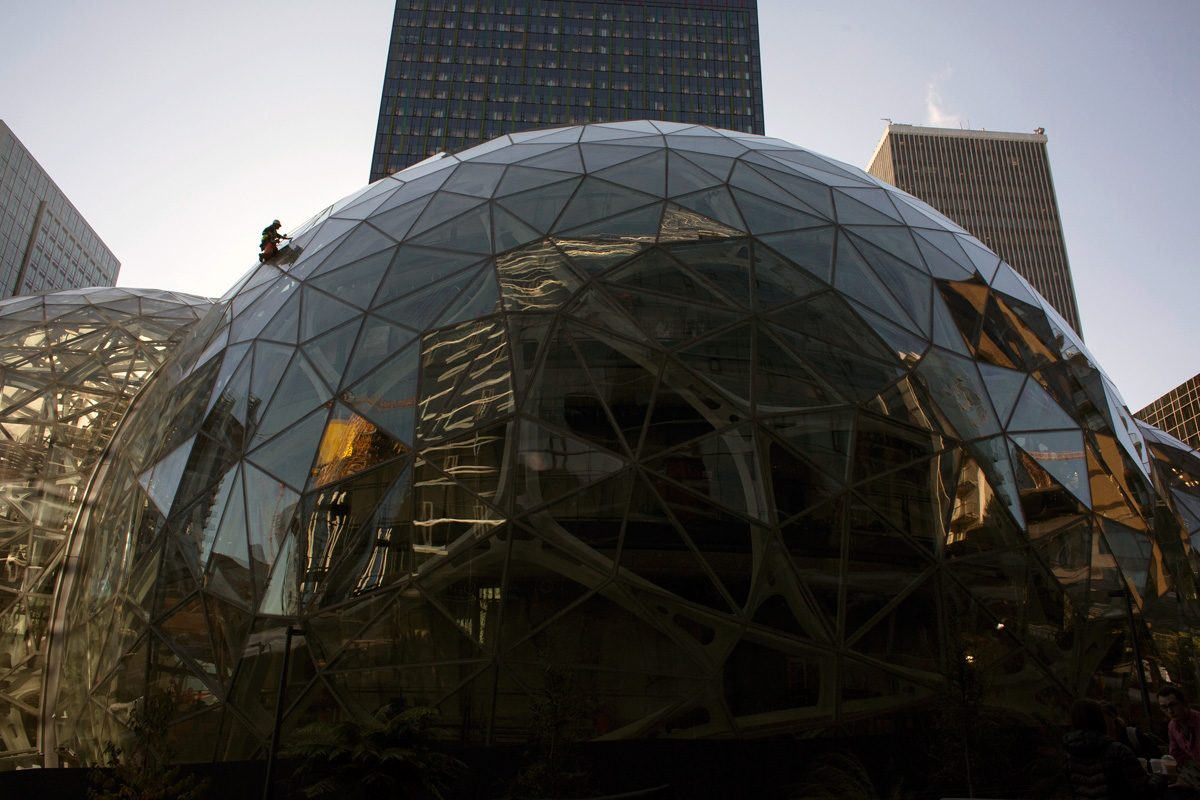 A worker cleans the exterior of one of three glass spheres at Amazon headquarters in Seattle.