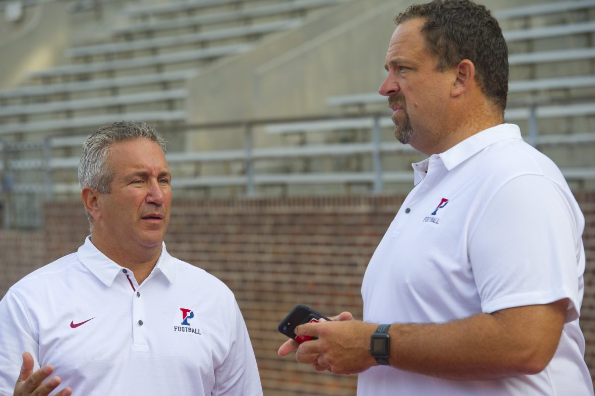 Penn coach Ray Priore (left) and offensive coordinator John Reagan talk during Penn Football's media day at Franklin Field in West Philadelphia.