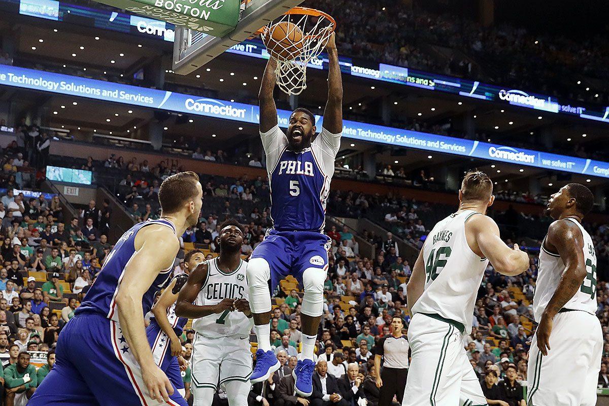 Philadelphia 76ers forward Amir Johnson dunks above Boston Celtics' Jaylen Brown during the first quarter of a preseason NBA basketball game in Boston, Monday, Oct. 9, 2017.